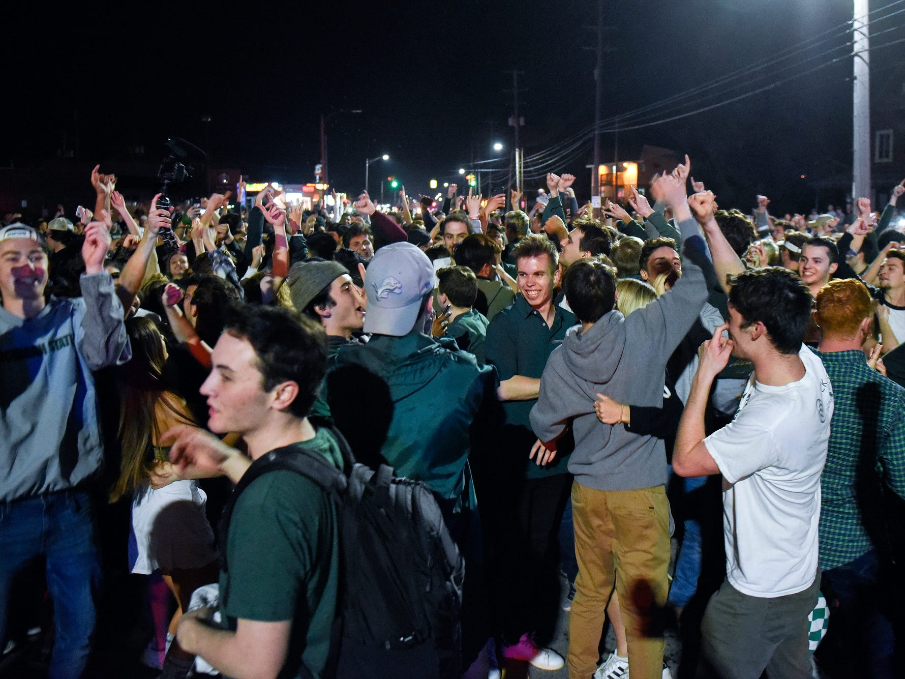 A group of people block Grand River Avenue near the Woodmere Avenue intersection after the Michigan State Spartans' Final Four loss to Texas Tech on Saturday, April 6, 2019, on in East Lansing.