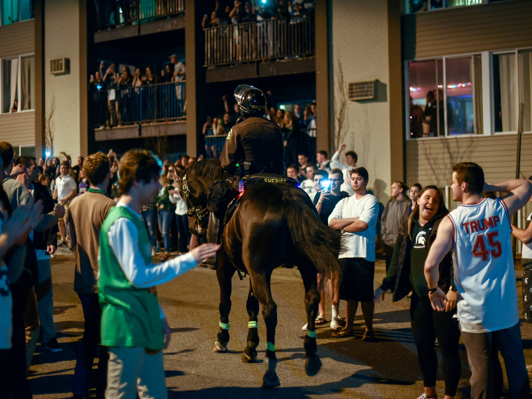 A police on horses make their way through the crowd at Waters Edge Drive and River Street after the Michigan State Spartans' Final Four loss to Texas Tech on Saturday, April 6, 2019, in East Lansing.