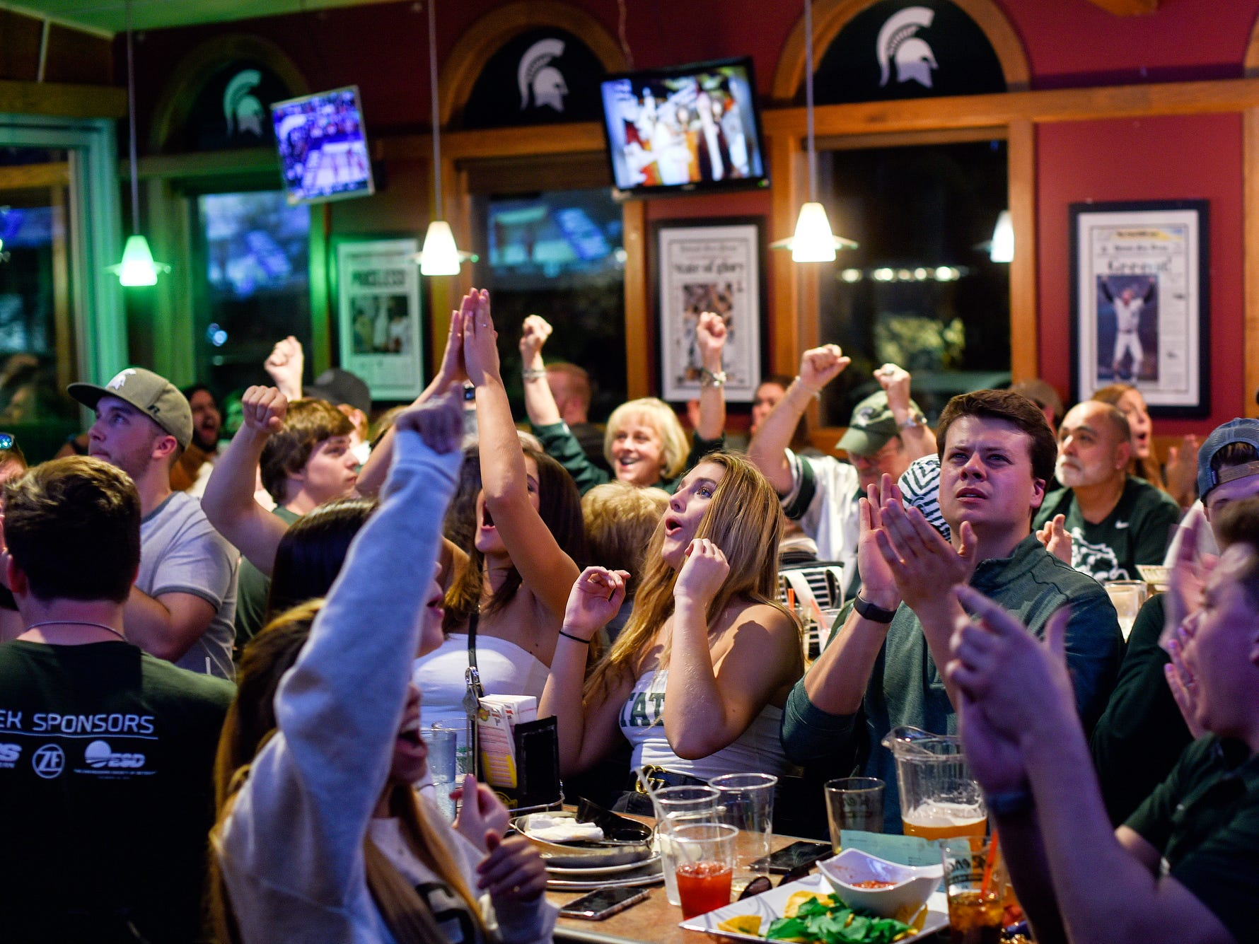 Fans react to a MSU score during the first half the Michigan State Spartans' Final Four game against Texas Tech on Saturday, April 6, 2019, at Reno's East in East Lansing.