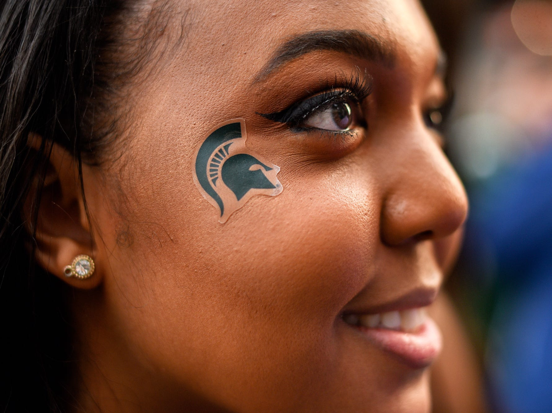 Michigan State University senior Brittany Thomas sports a Spartans logo on her cheek as she waits to get inside the FieldHouse to watch the Michigan State Spartans' Final Four game against Texas Tech on Saturday, April 6, 2019, in East Lansing.