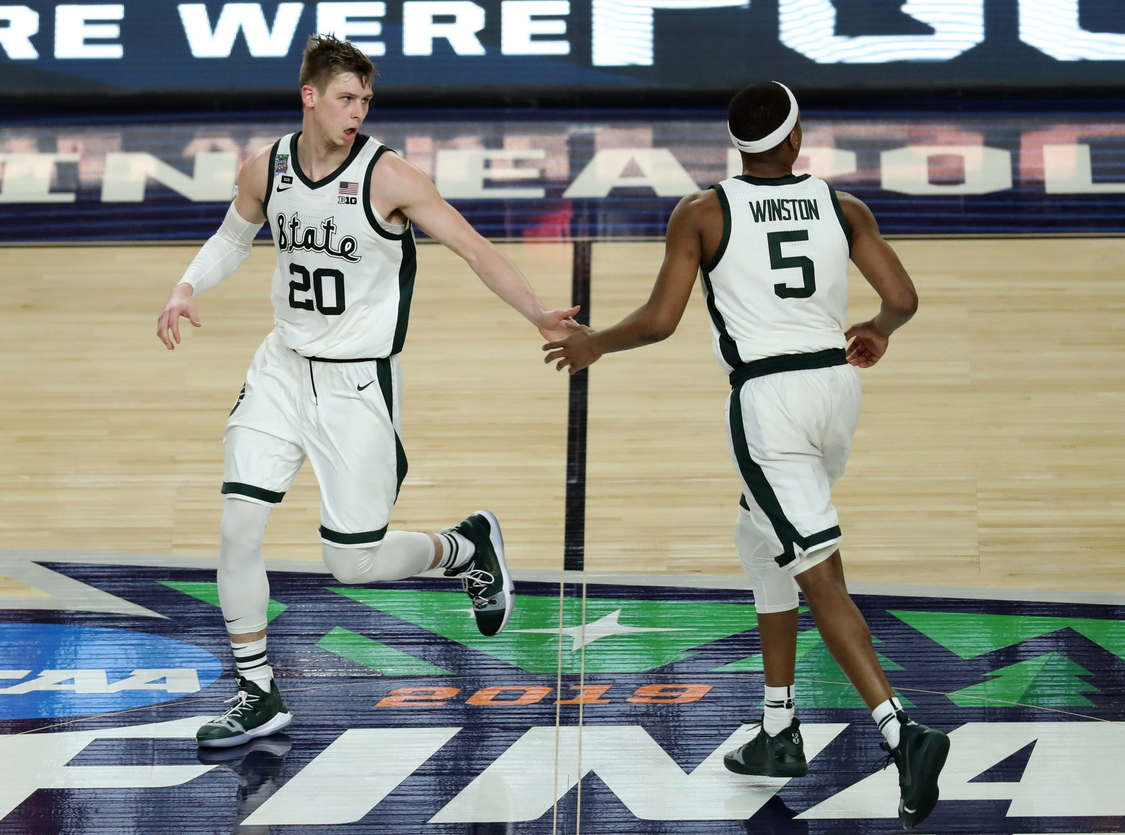 Apr 6, 2019; Minneapolis, MN, USA; Michigan State Spartans guard Matt McQuaid (20) and guard Cassius Winston (5) high five during the second half against the Texas Tech Red Raiders in the semifinals of the 2019 men's Final Four at US Bank Stadium. Mandatory Credit: Brace Hemmelgarn-USA TODAY Sports