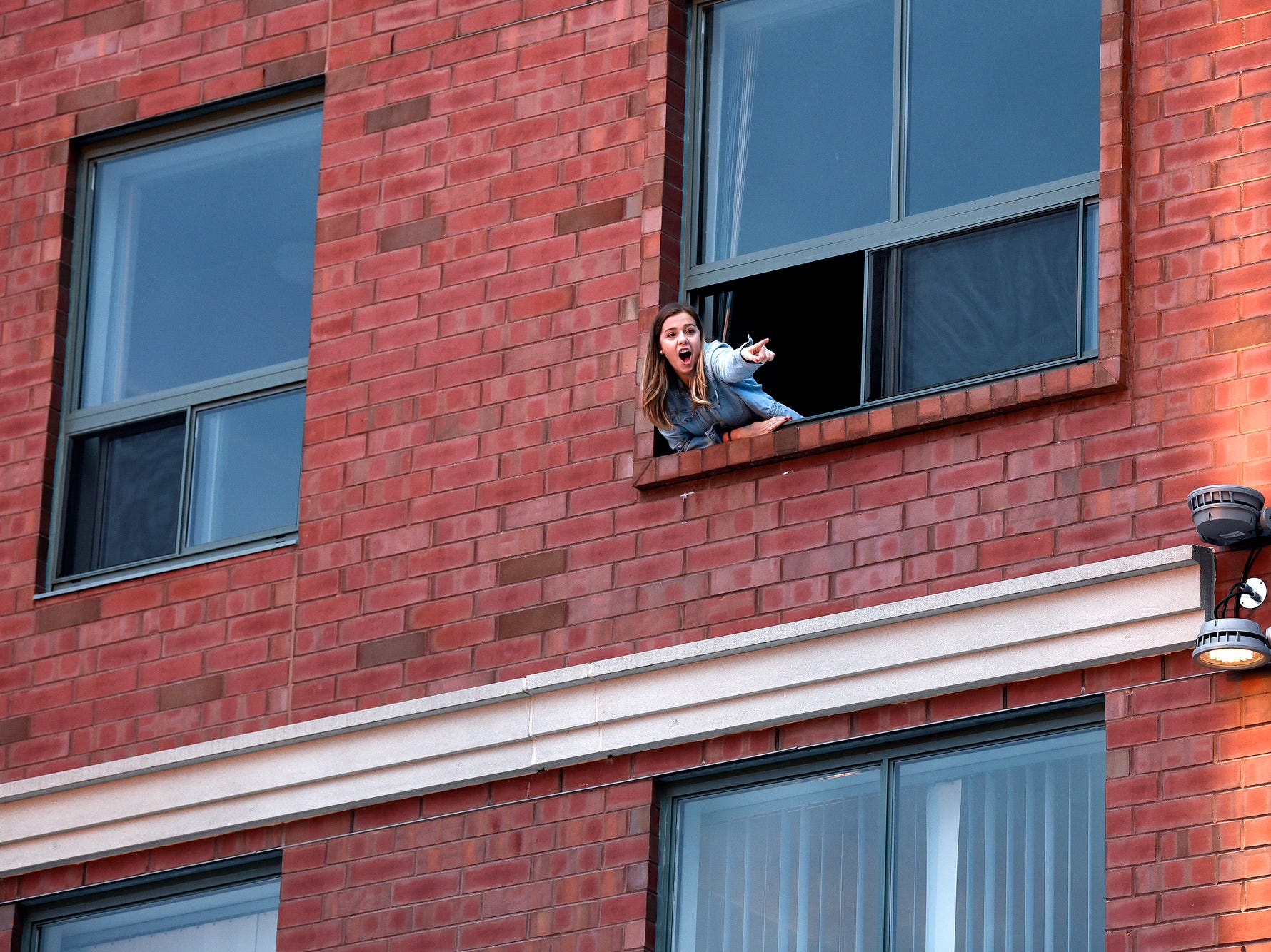 "A Spartans fan yells out ""go green"" to passerbys from an apartment window several floors up street level on Grove Street before the Michigan State Spartans' Final Four game against Texas Tech on Saturday, April 6, 2019, in downtown East Lansing."
