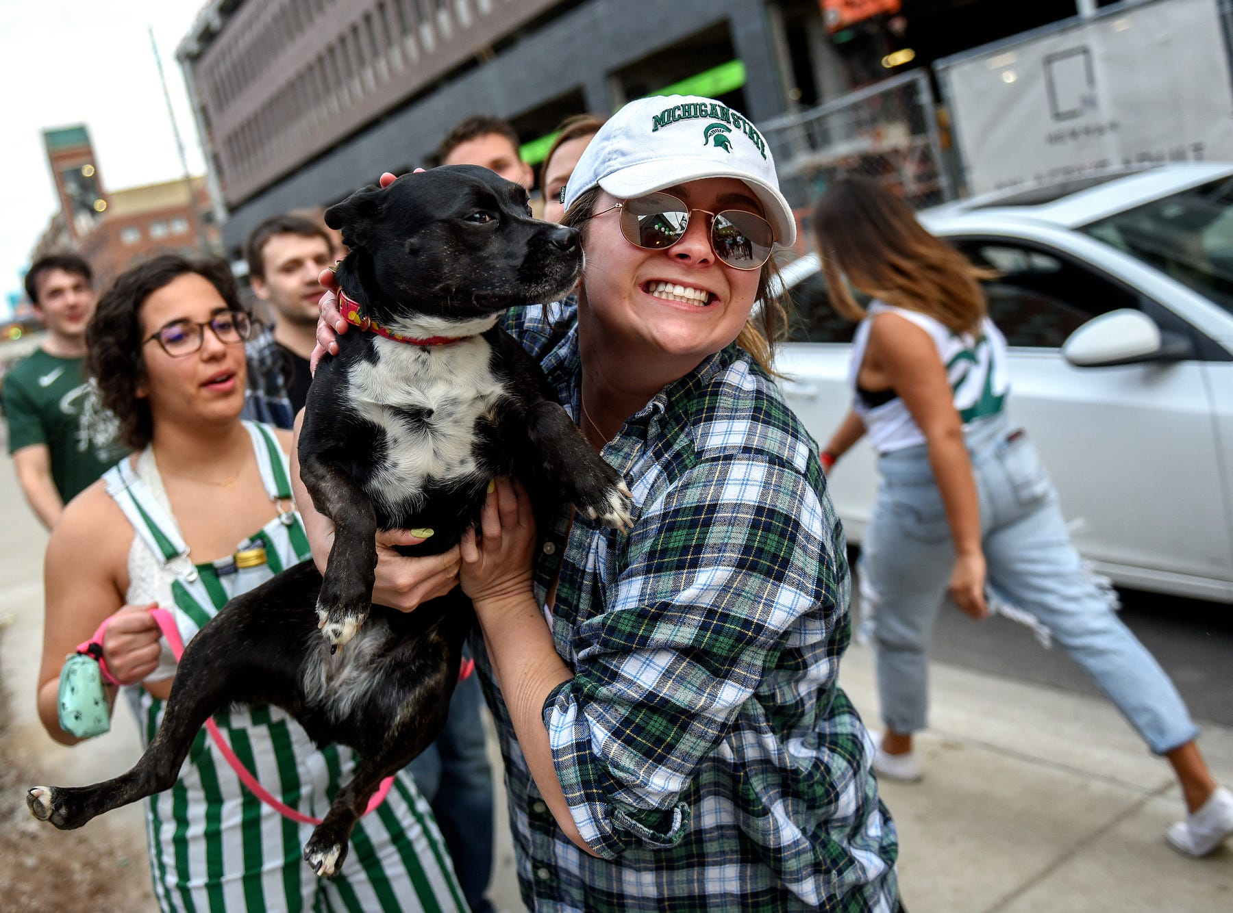Megan Fleischmann holds up her dog Lola as she walks around downtown East Lansing with friends before the Michigan State Spartans' Final Four game against Texas Tech on Saturday, April 6, 2019.