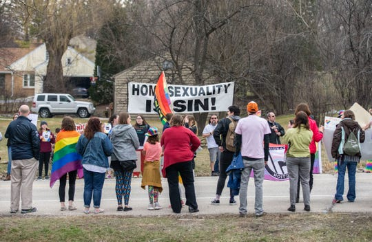 Protestors (background) face off against supporters of the Drag Queen Story Hour event at Unitarian Universalist Church West in Brookfield on Sunday, April 7.