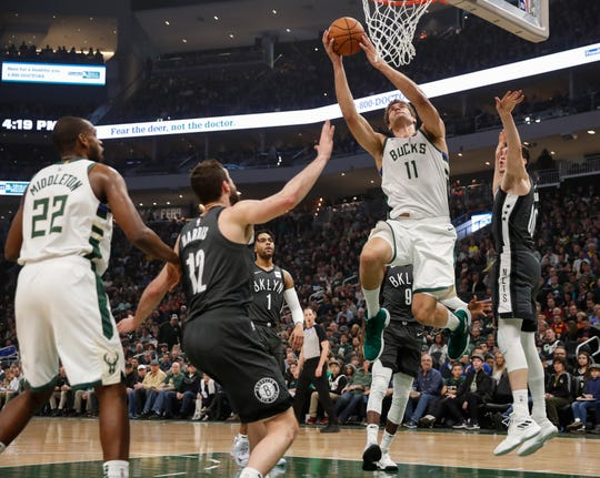 Bucks center Brook Lopez goes up for a shot while surrounded by Nets defenders Sunday.