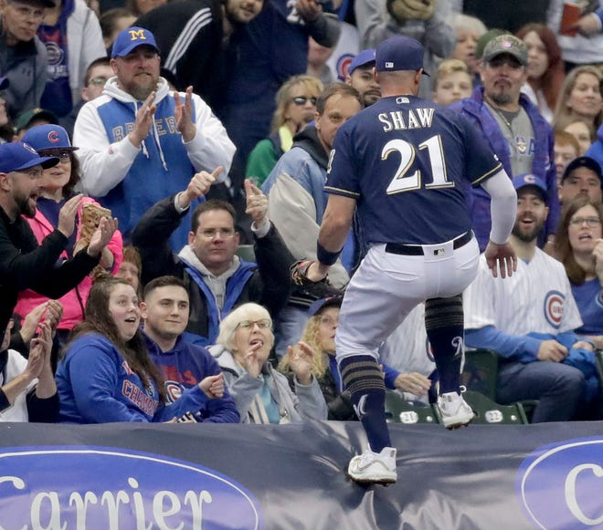 Brewers third baseman Travis Shaw  jumps on the tarp after catching a foul pop off the bat of the Cubs' Jason Heyward during the third inning.