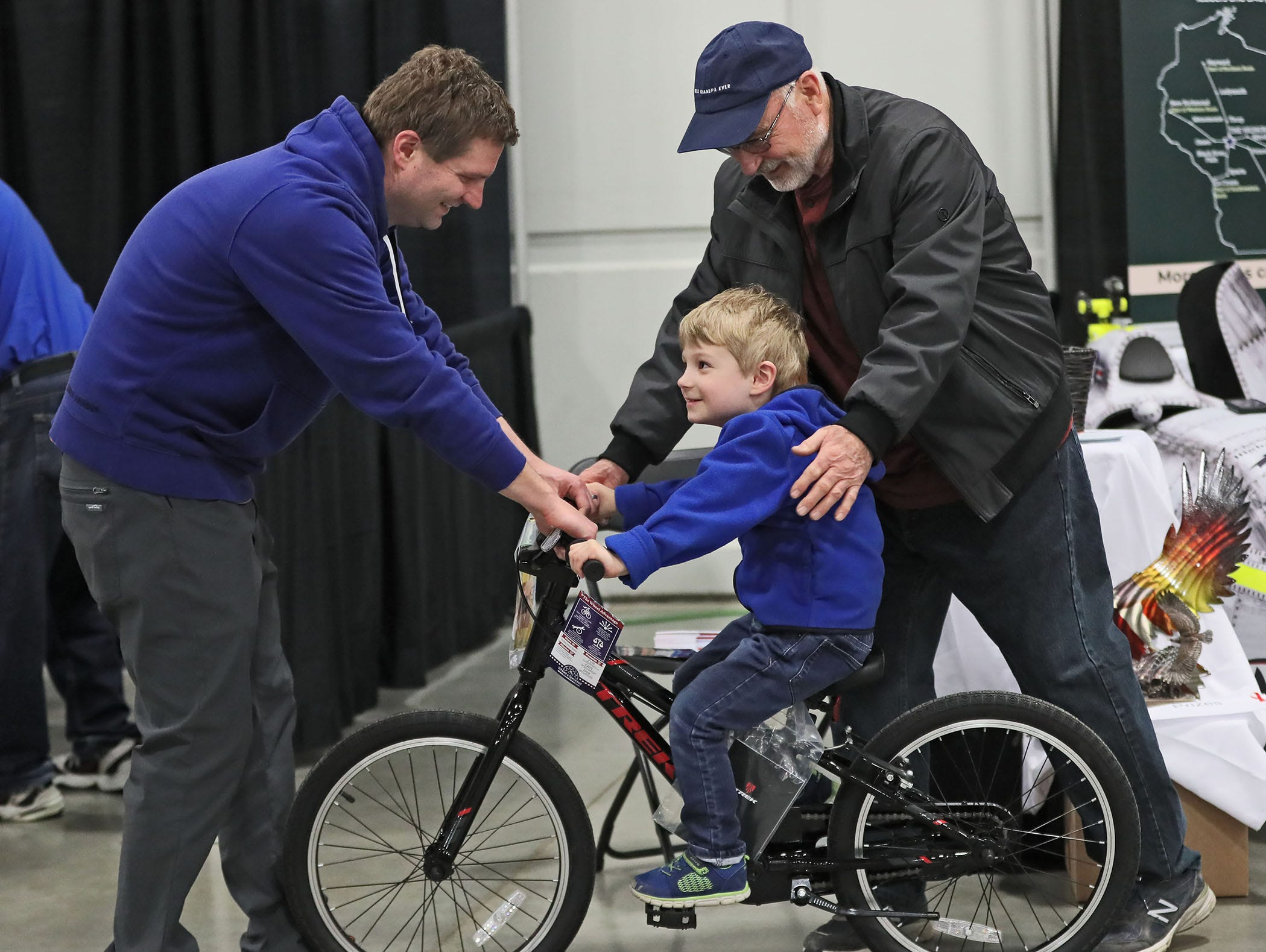 Tom Giever, left, of Muskego helps his son Thomas, 4, get the feel for a bike, with the help of his father-in-law, Don Richter of Muskego.