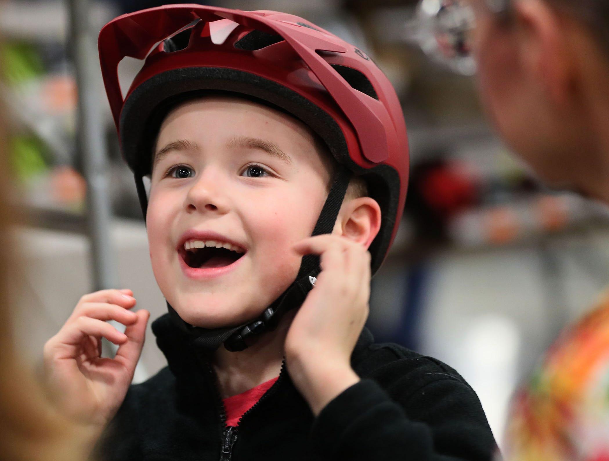 Will Weber, 8, of Wauwatosa tries on a new bike helmet.