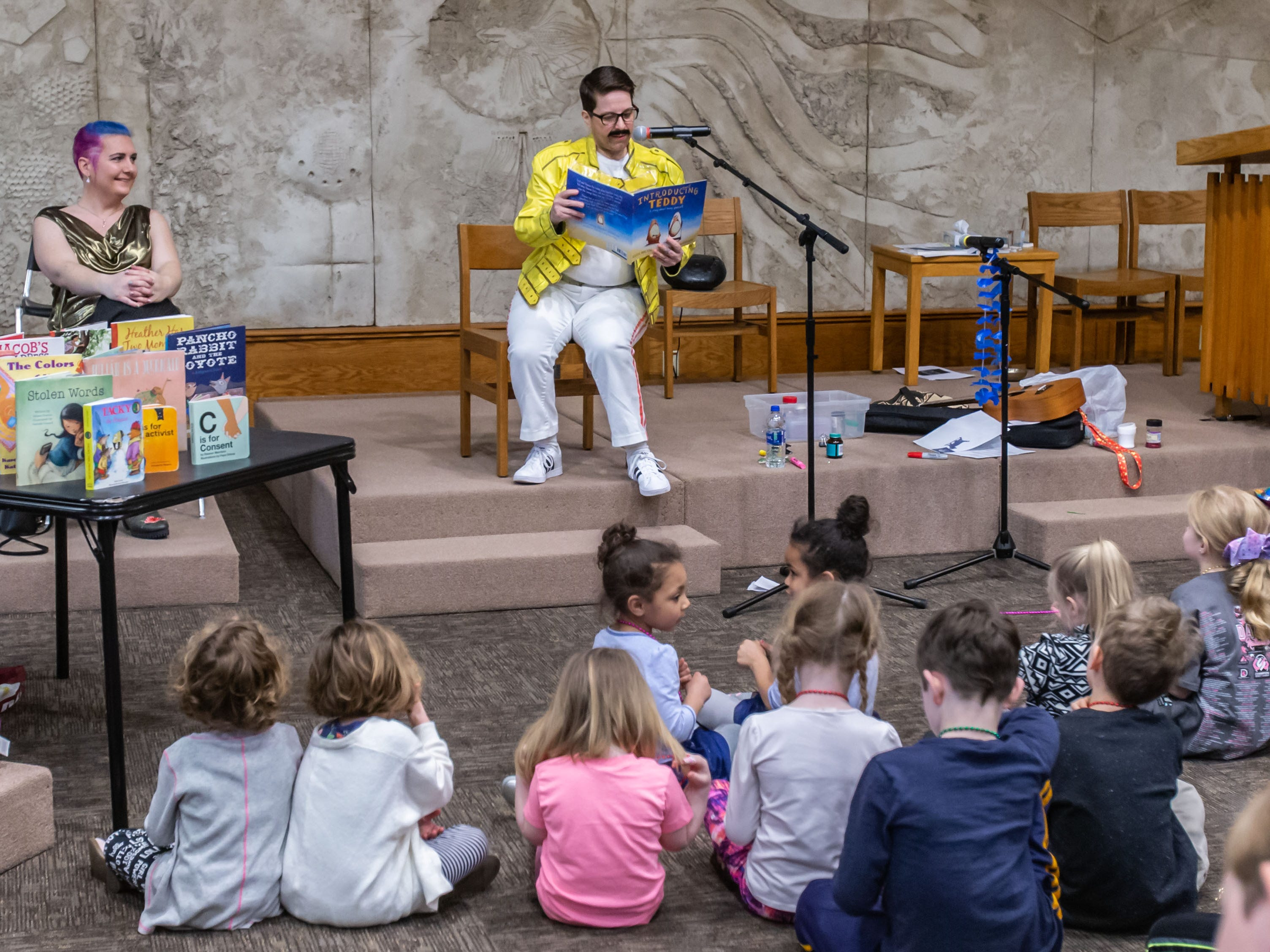 Event organizer Edie Pasek (left) looks on as Mr. Fitswell reads to visitors during Drag Queen Story Hour (DQSH) at Unitarian Universalist Church West in Brookfield on Sunday, April 7, 2019. According to organizers, DQSH is drag queens reading stories. DQSH captures the imagination and play of the gender fluidity of childhood and gives kids glamorous, positive, and unabashedly queer role models. kids are able to see people who defy rigid gender restrictions and imagine a world where people can present as they wish, where dress up is real.