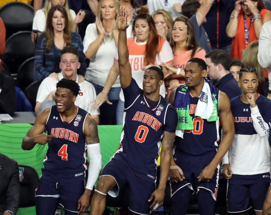 Auburn players Malik Dunbar (4), Horacr Spencer (0) Austin Wiley (50) and Myles Barker (right) celebrate on the bench during the second half against Virginia in the Final Four at US Bank Stadium on April 6, 2019, in Minneapolis.