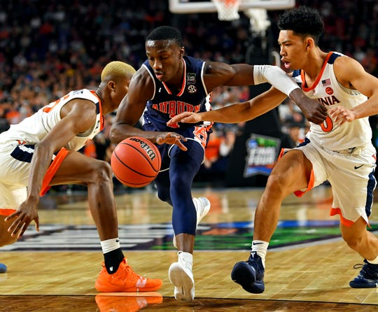 Auburn Tigers guard Jared Harper (1) drives to the basket against Virginia Cavaliers guard Kihei Clark (0) during the second half in the semifinals of the 2019 men's Final Four at US Bank Stadium.