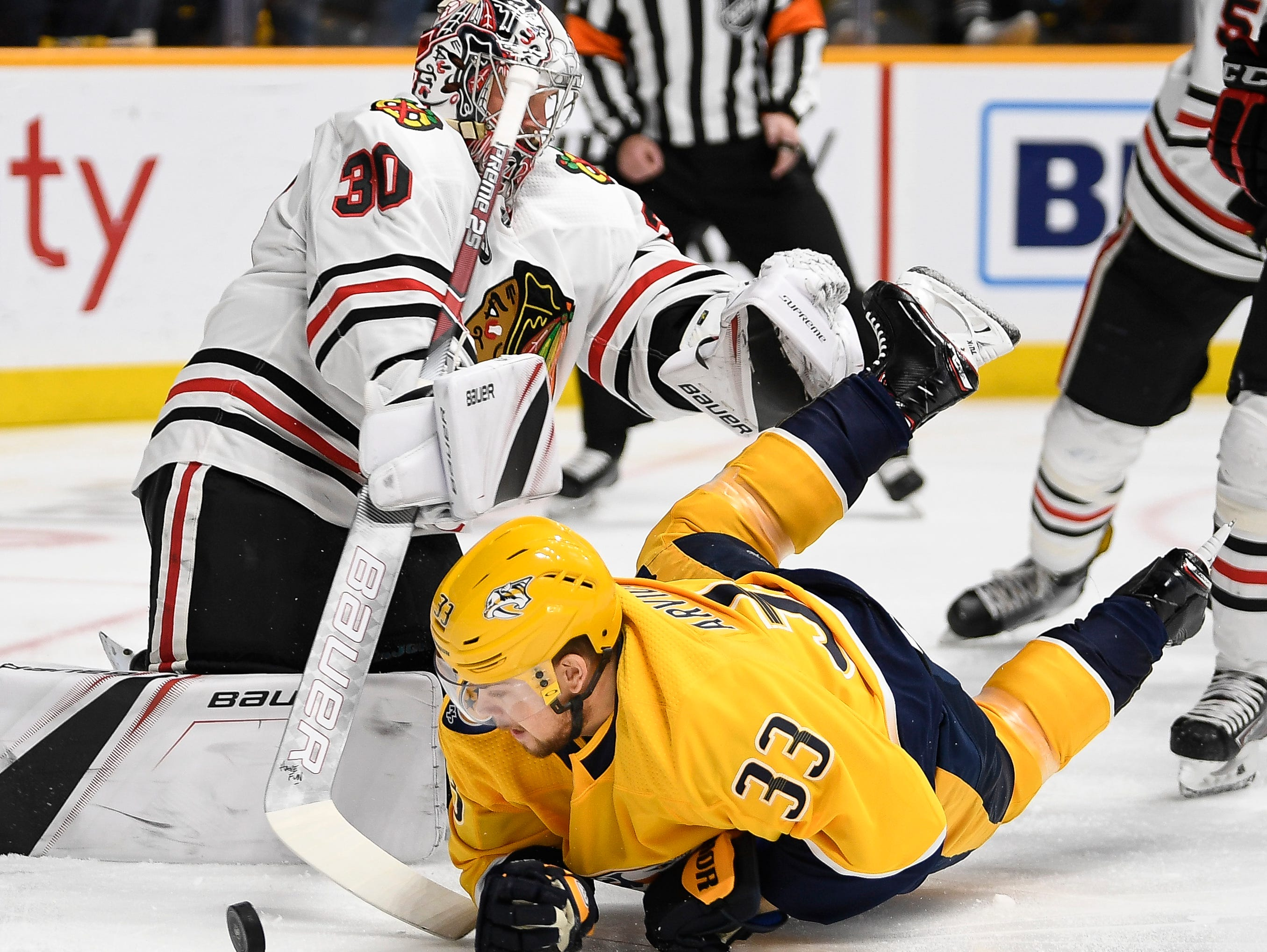 Nashville Predators right wing Viktor Arvidsson (33) falls to the ice beside Chicago Blackhawks goaltender Cam Ward (30) during the first period at Bridgestone Arena in Nashville, Tenn., Saturday, April 6, 2019.