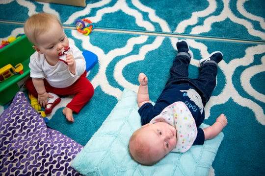 Wrenley Sunderlin, left, 13 months, chews on her sock during day care at Fannie Battle Day Home on March 28.
