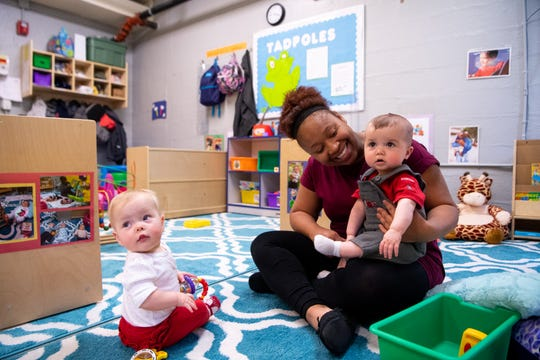 Wrenley Sunderlin, 13 months, looks over her shoulder as Miltica Bassham holds Dylan Maphis, 5 months, during day care at Fannie Battle Day Home on March 28 in Nashville. East End Prep teachers struggled to find day care options and remain in their positions. As a result, administrators created the infant room for teachers' children at a lower cost and aligning with their schedules.