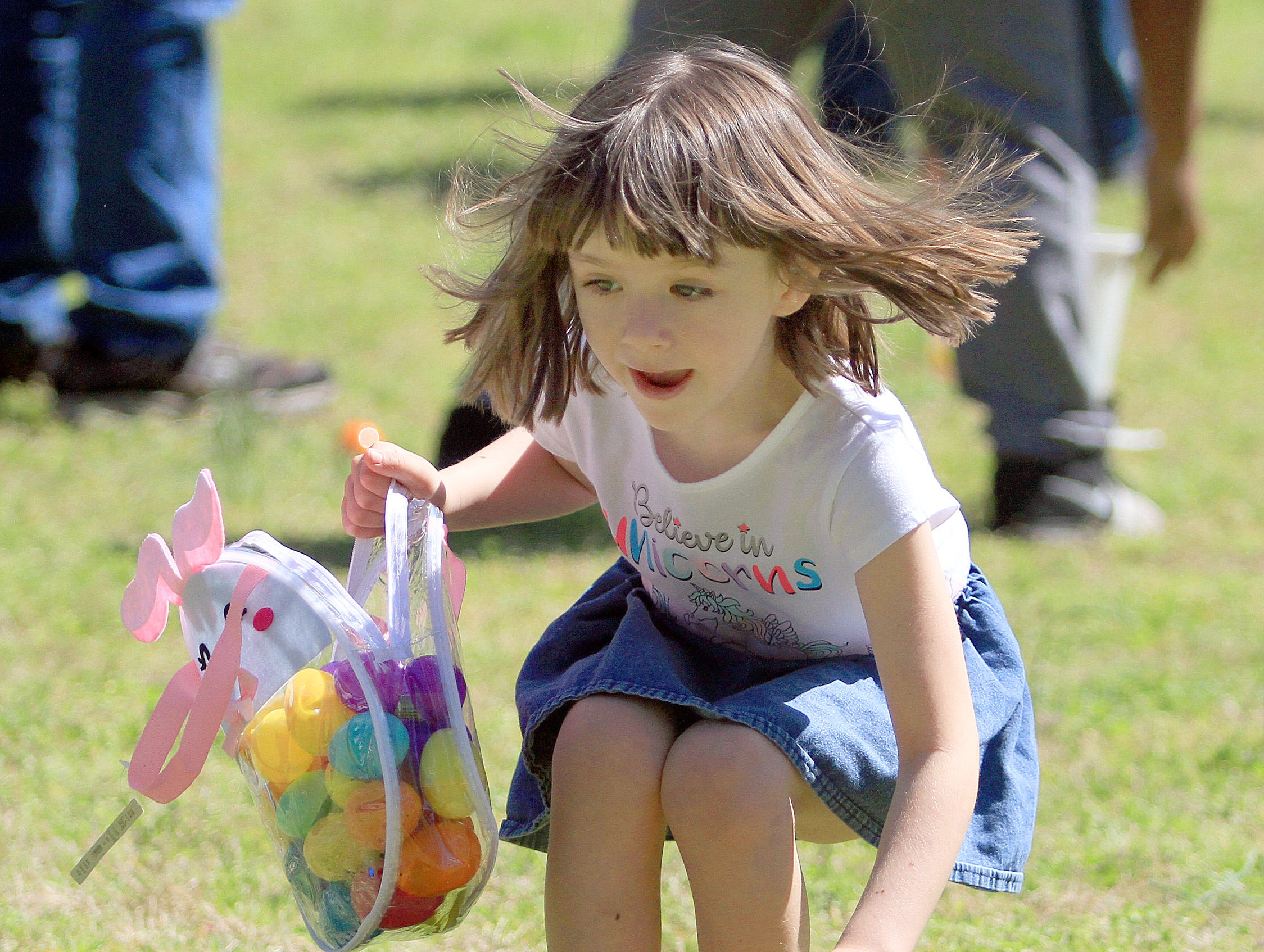 A young girl scrambles for Easter eggs at Rock Castle in Hendersonville, TN on Saturday, April 6, 2019.
