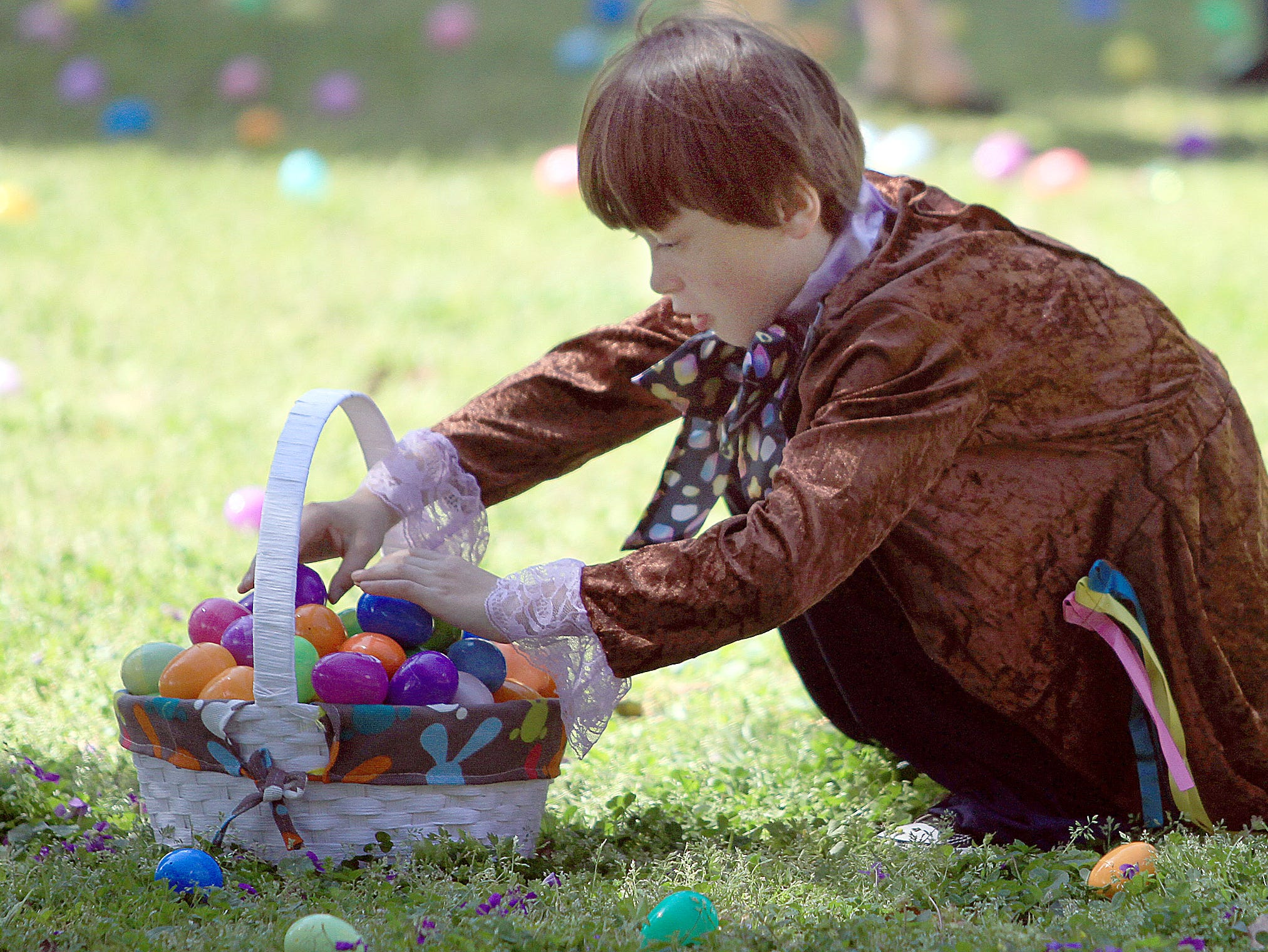 A young man tries to keep his eggs from falling out of his basket at the egg hunt at Rock Castle in Hendersonville, TN on Saturday, April 6, 2019.