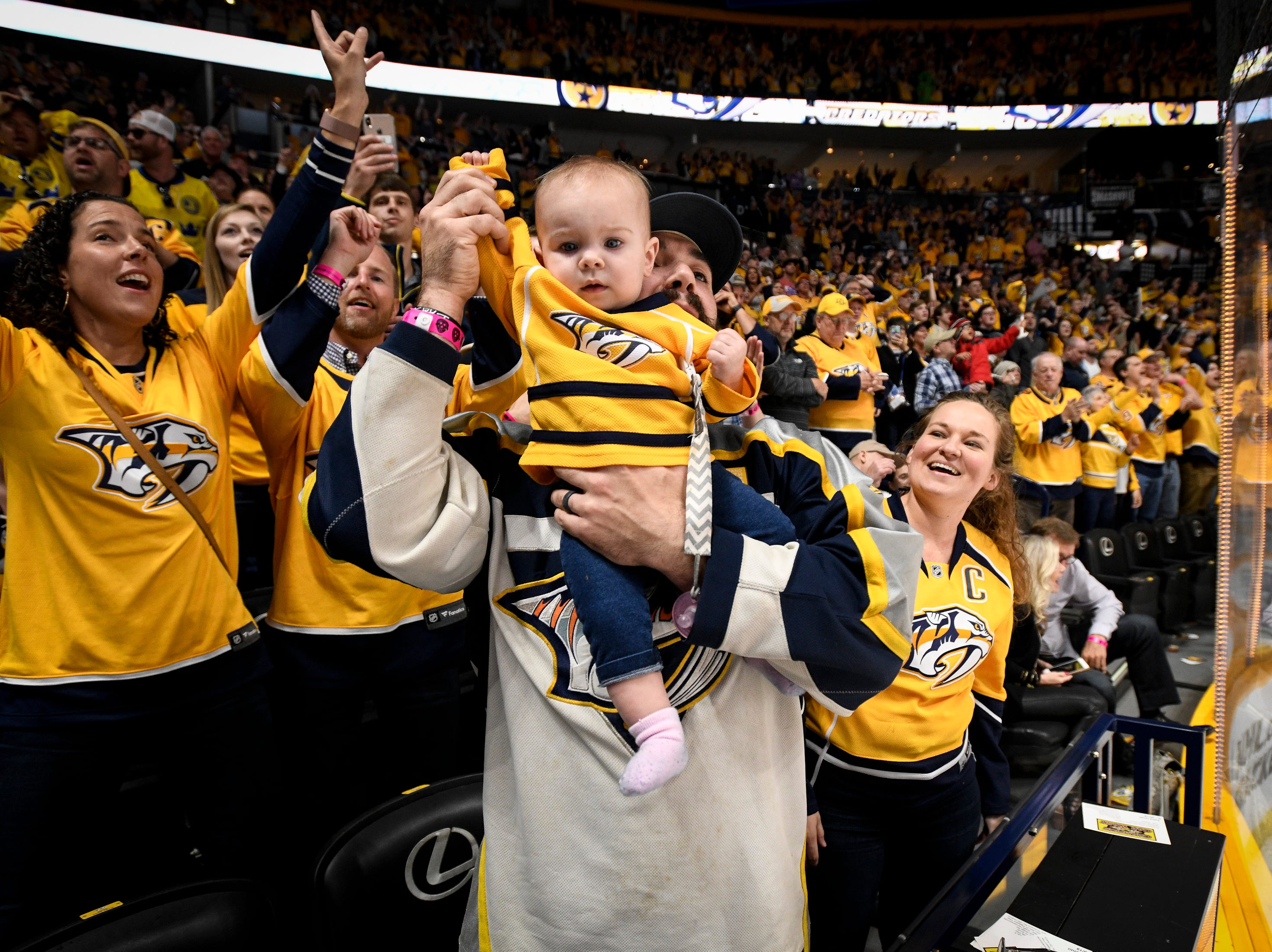 Jared Prall holds up his 9-month-old daughter Preslee Prall after Nashville Predators left wing Filip Forsberg scored against the Chicago Blackhawks during the second period at Bridgestone Arena in Nashville, Tenn., Saturday, April 6, 2019.