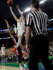 Virginia's Kyle Guy (5) takes a shot as Auburn's Samir Doughty (10) was called foul during the second half in the semifinals of the Final Four NCAA college basketball tournament, Saturday, April 6, 2019, in Minneapolis.