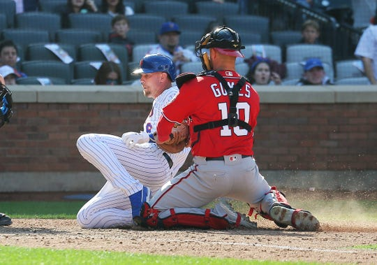 Apr 6, 2019; New York City, NY, USA; New York Mets pinch hitter Jeff McNeil (6) is tagged out at home plate by Washington Nationals catcher Yan Gomes (10) after being caught in a rundown during the eighth inning at Citi Field.