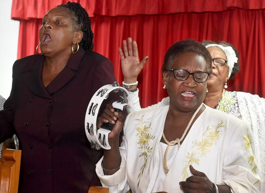 Members of the congregation of Mount Pleasant Baptist Church, one of three churches destroyed by fire over the last week, sing praises during Sunday services at Morning Star Baptist Church.