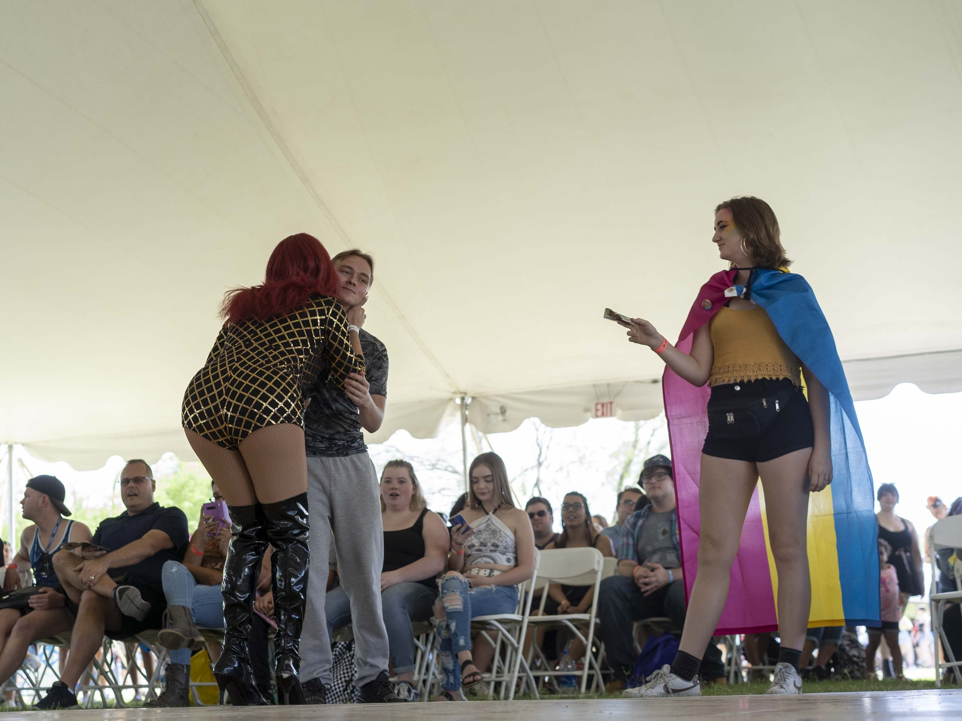 Drag queen Kim Etiquette performs while fans pay tips during Phoenix Pride at Steele Indian School Park on Saturday, April 6, 2019.