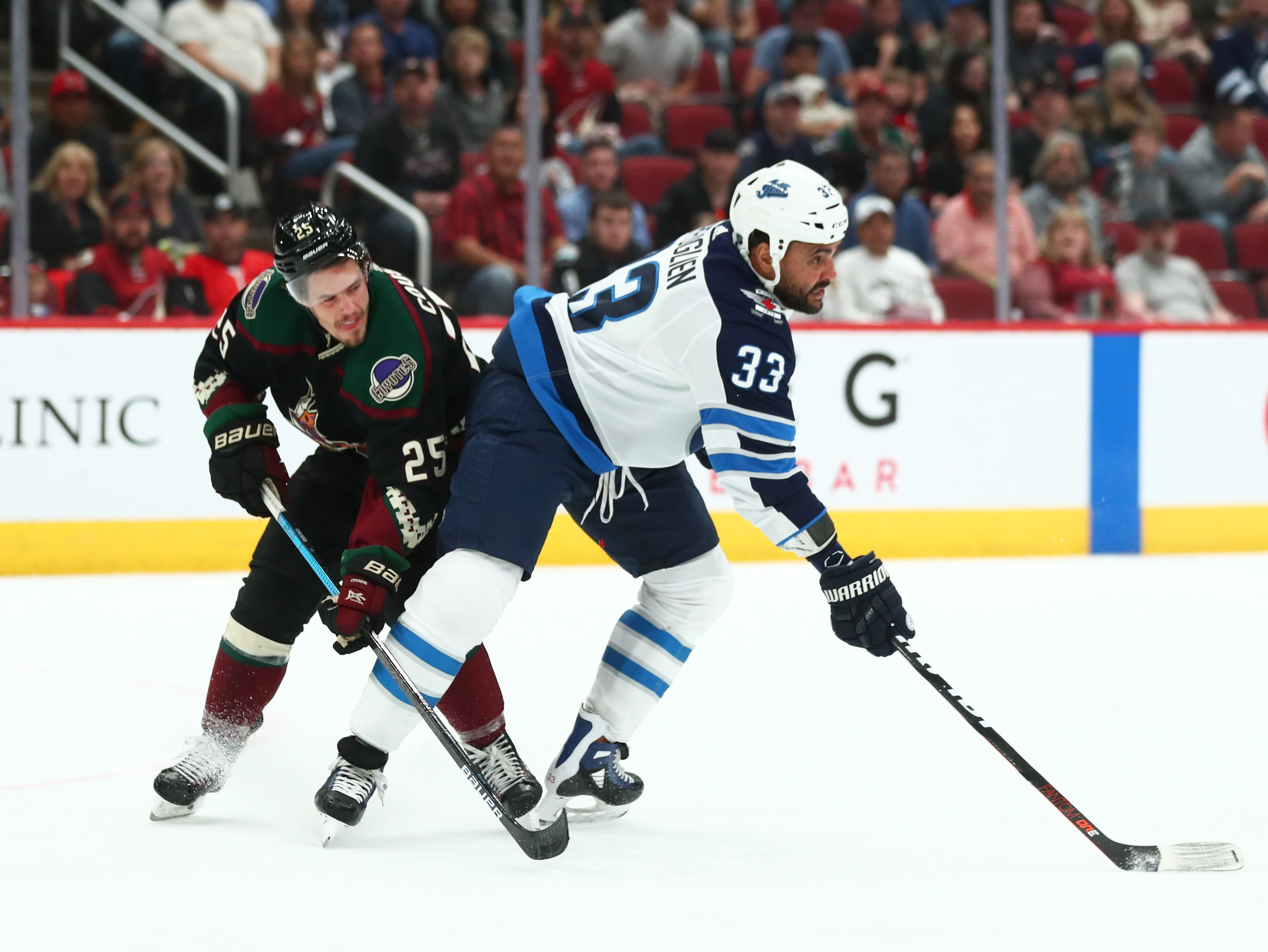 Apr 6, 2019; Glendale, AZ, USA; Arizona Coyotes center Nick Cousins (25) battles for the puck against Winnipeg Jets defenseman Dustin Byfuglien (33) in the first period at Gila River Arena. Mandatory Credit: Mark J. Rebilas-USA TODAY Sports