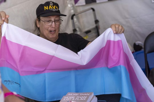 Monica Helms, who created the transgender pride flag, signs books during Phoenix Pride at Steele Indian School Park on April 6, 2019.