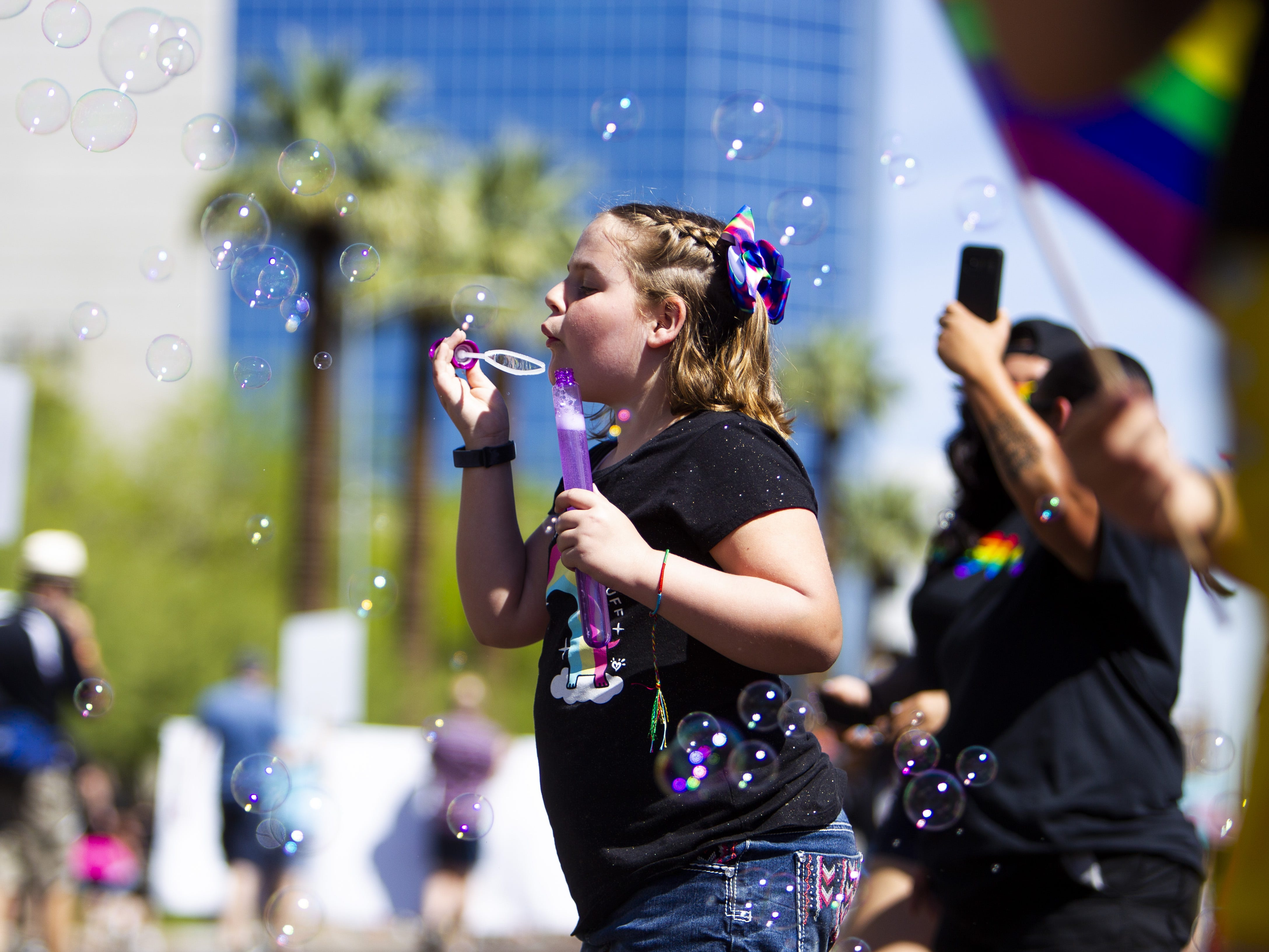 A girl blows bubbles during the Phoenix Pride Parade on April 7, 2019.