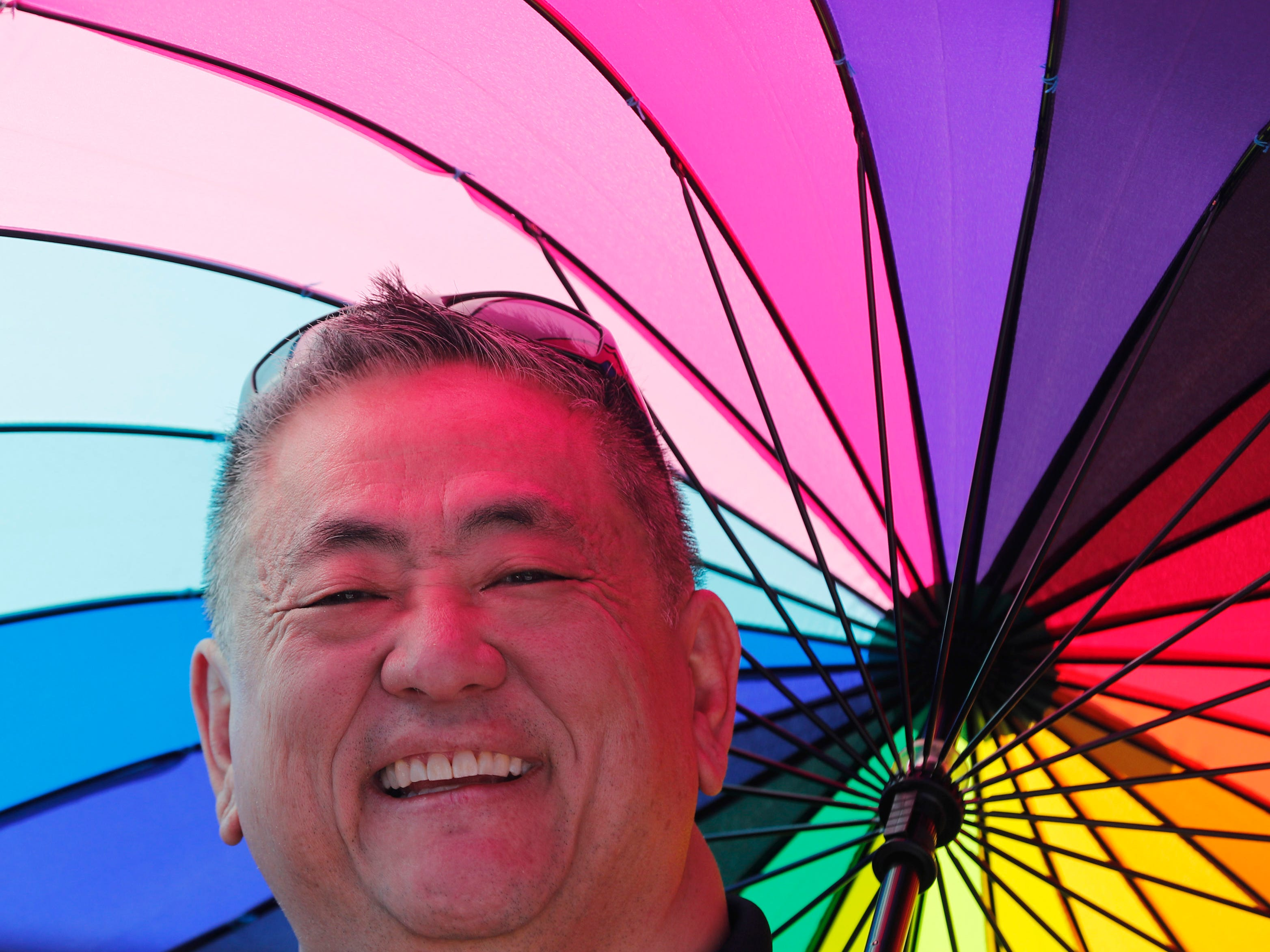 Randy Ichiuji holds and umbrella during the Phoenix Pride Parade on April 7, 2019.