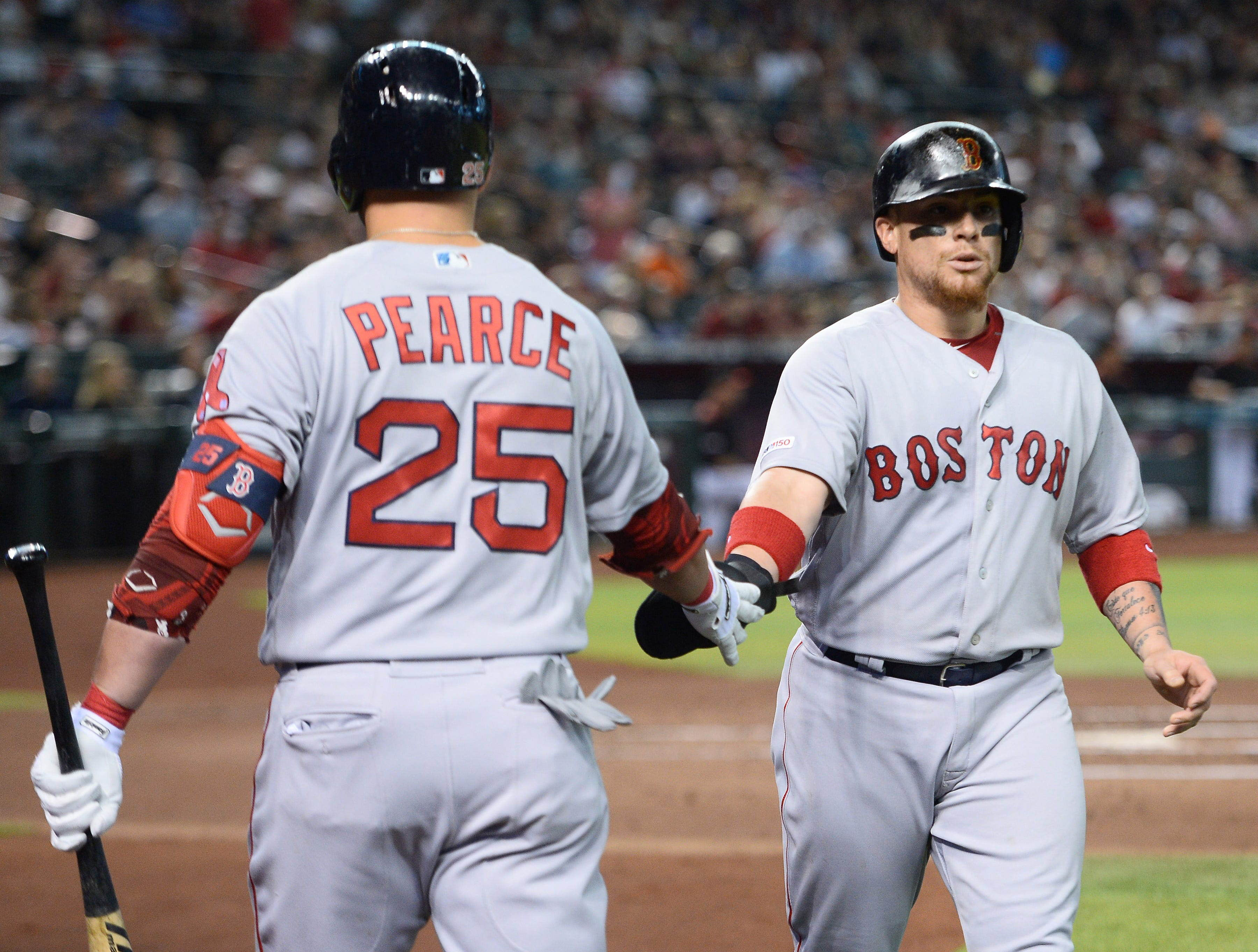 Apr 6, 2019; Phoenix, AZ, USA; Boston Red Sox catcher Christian Vazquez (7) slaps hands with Boston Red Sox first baseman Steve Pearce (25) after scoring a run against the Arizona Diamondbacks during the second inning at Chase Field. Mandatory Credit: Joe Camporeale-USA TODAY Sports