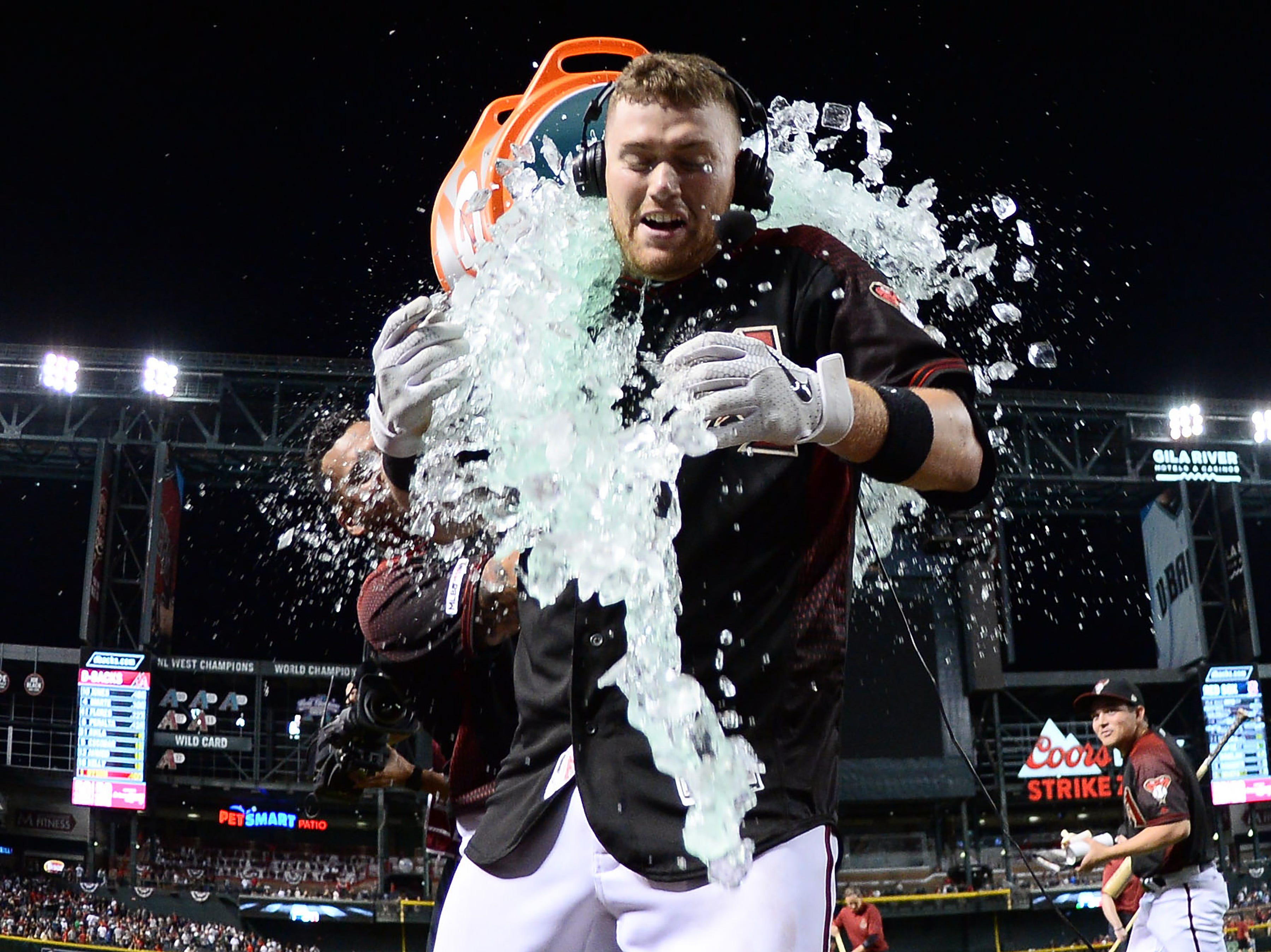 Apr 6, 2019; Phoenix, AZ, USA; Arizona Diamondbacks catcher Carson Kelly (18) is doused with Gatorade by Arizona Diamondbacks right fielder David Peralta (6) after ninth inning walk off single against the Boston Red Sox at Chase Field. Mandatory Credit: Joe Camporeale-USA TODAY Sports