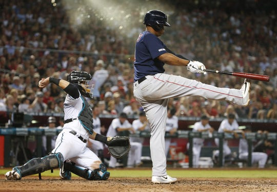 Boston Red Sox third baseman Rafael Devers (11) hits his shoe after taking a strike on Opening Day against the Arizona Diamondbacks at Chase Field in Phoenix on April 5.