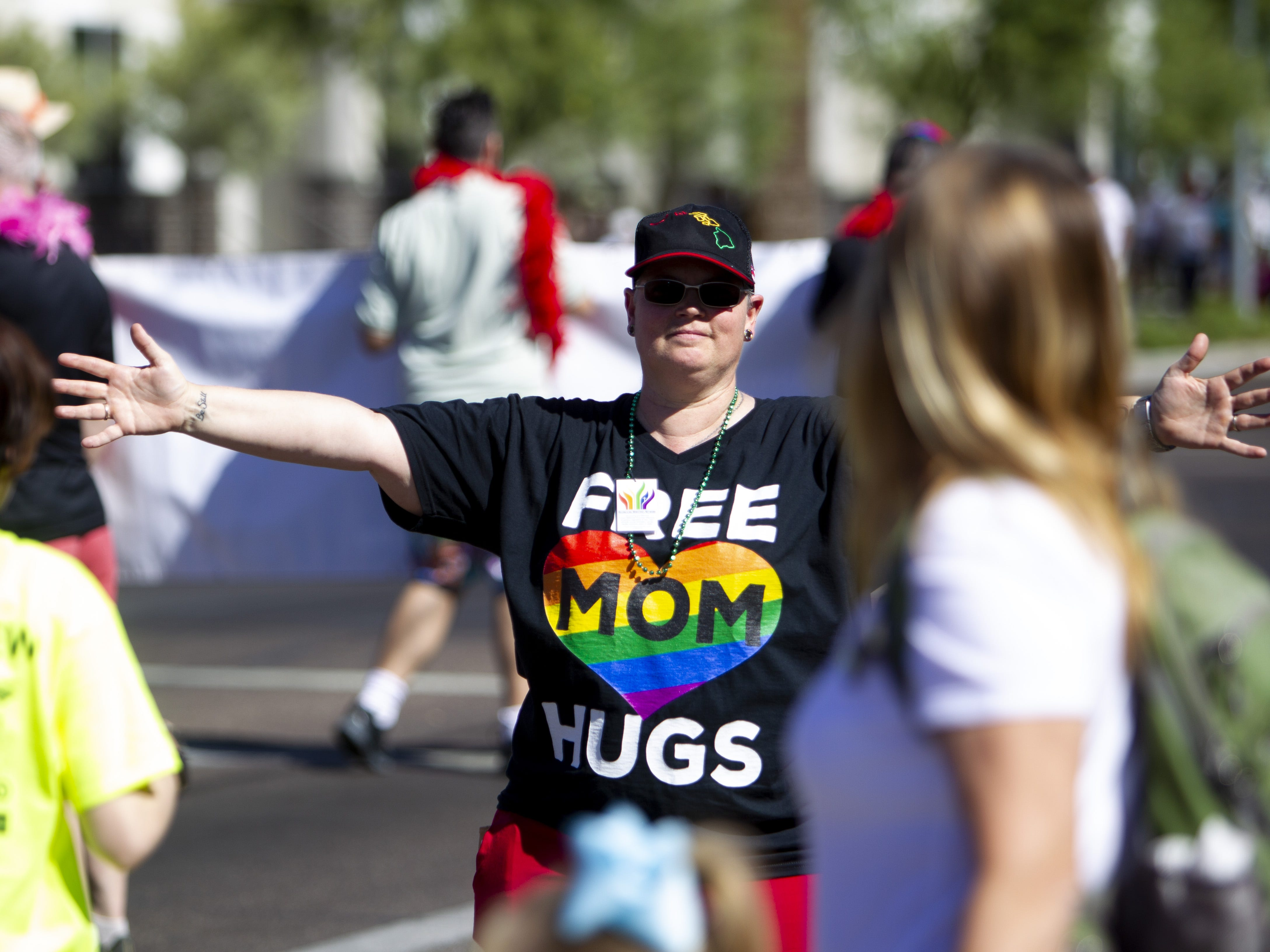 """A woman offers """"free mom hugs"""" in the staging area before the Phoenix Pride Parade on April 7, 2019."""