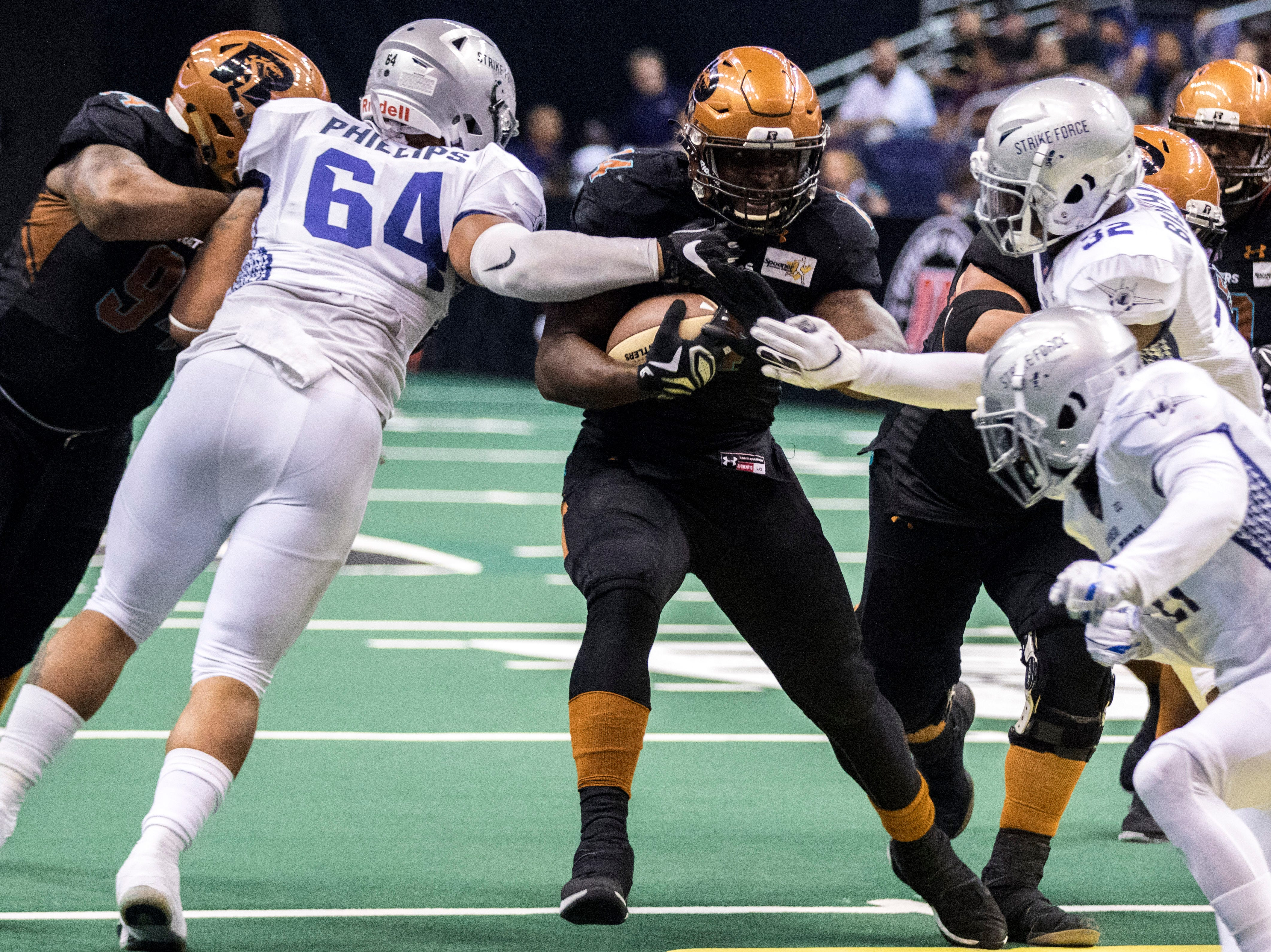 Arizona Rattlers' Darrell Monroe runs between tackles against San Diego Strike Force's defense during the first half of their game at Talking Stick Resort Arena in Phoenix Friday, April. 6, 2019.