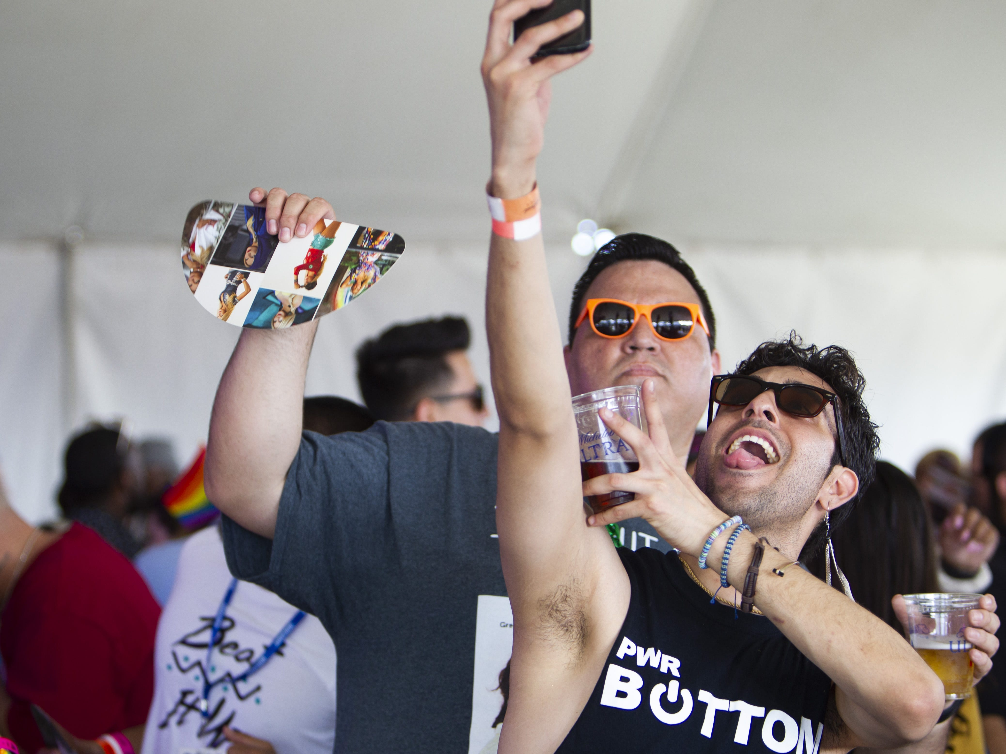 Eric Balderas, left, and Carlos Rodriguez take a selfie together during Phoenix Pride at Steele Indian School Park on Saturday, April 6, 2019.
