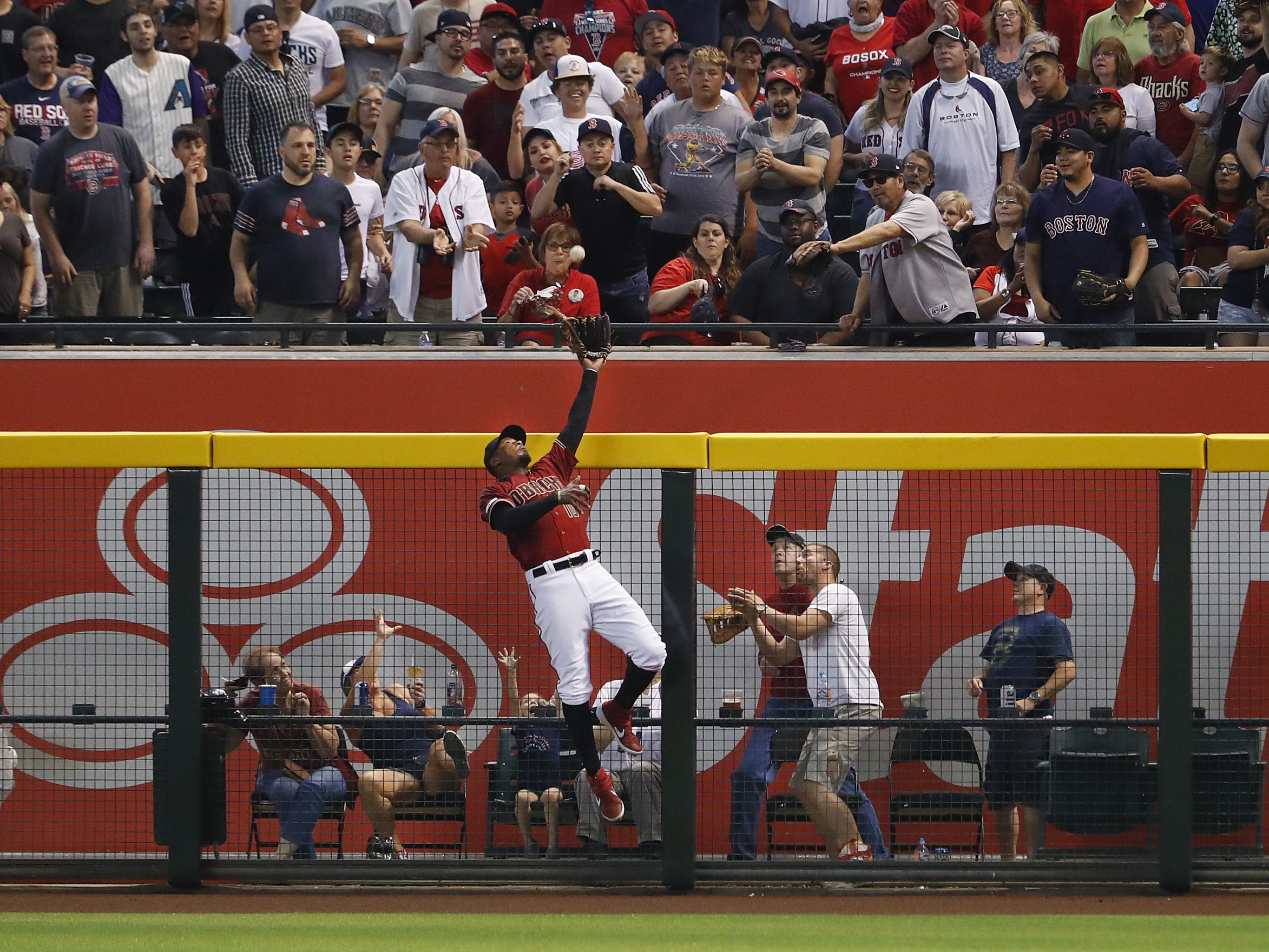 Diamondbacks Adam Jones (10) jumps at the wall but is unable to rob Red Sox Mitch Moreland (18) of his home run during the seventh inning at Chase Field in Phoenix, Ariz. on April 7, 2019.