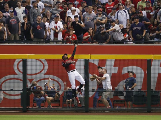 Adam Jones jumps at the wall but is unable to rob Mitch Moreland of his home run in the seventh inning of Sunday's Diamondbacks loss.