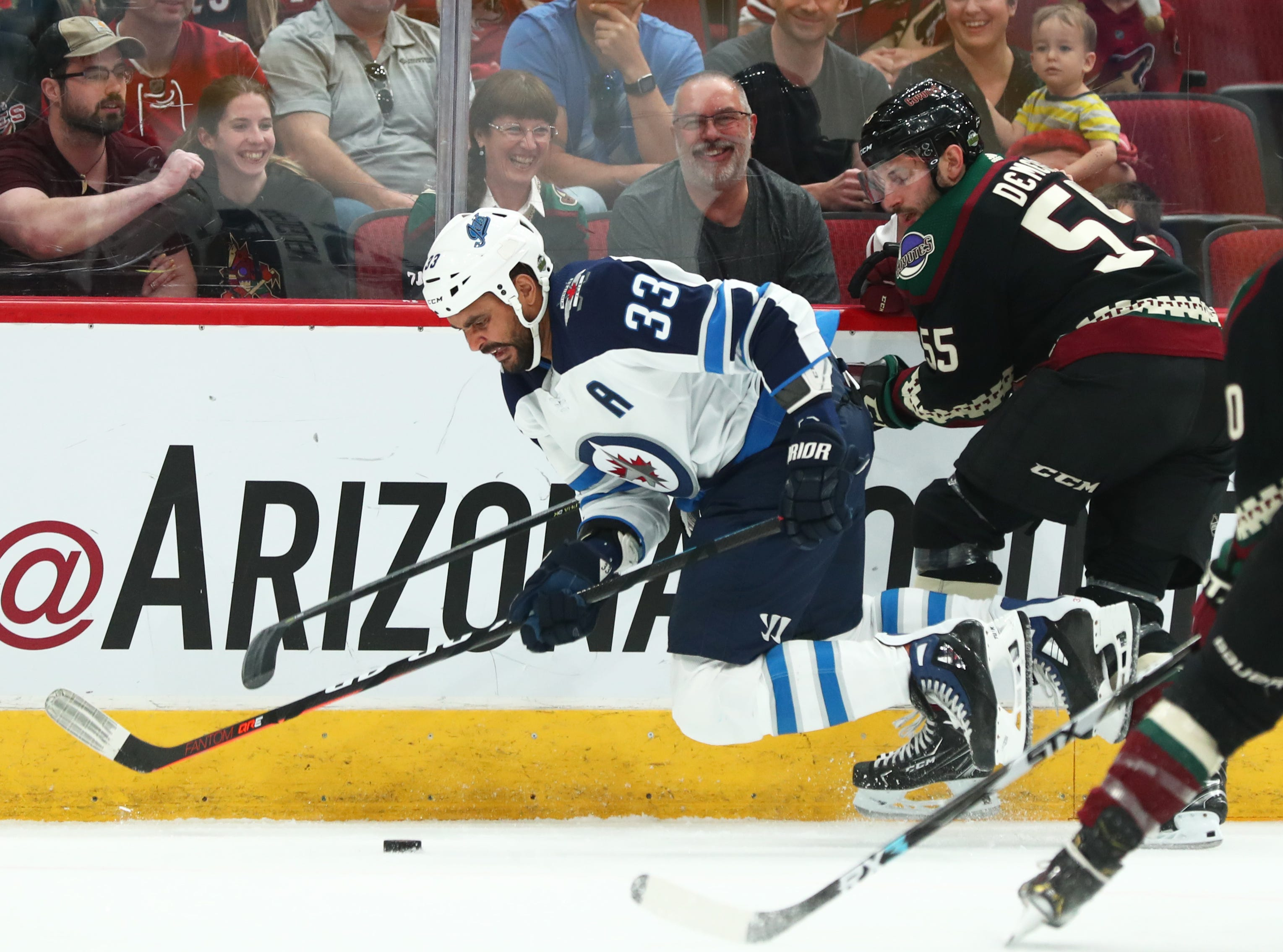 Apr 6, 2019; Glendale, AZ, USA; Winnipeg Jets defenseman Dustin Byfuglien (33) is tripped up by Arizona Coyotes defenseman Jason Demers (55) in the first period at Gila River Arena. Mandatory Credit: Mark J. Rebilas-USA TODAY Sports