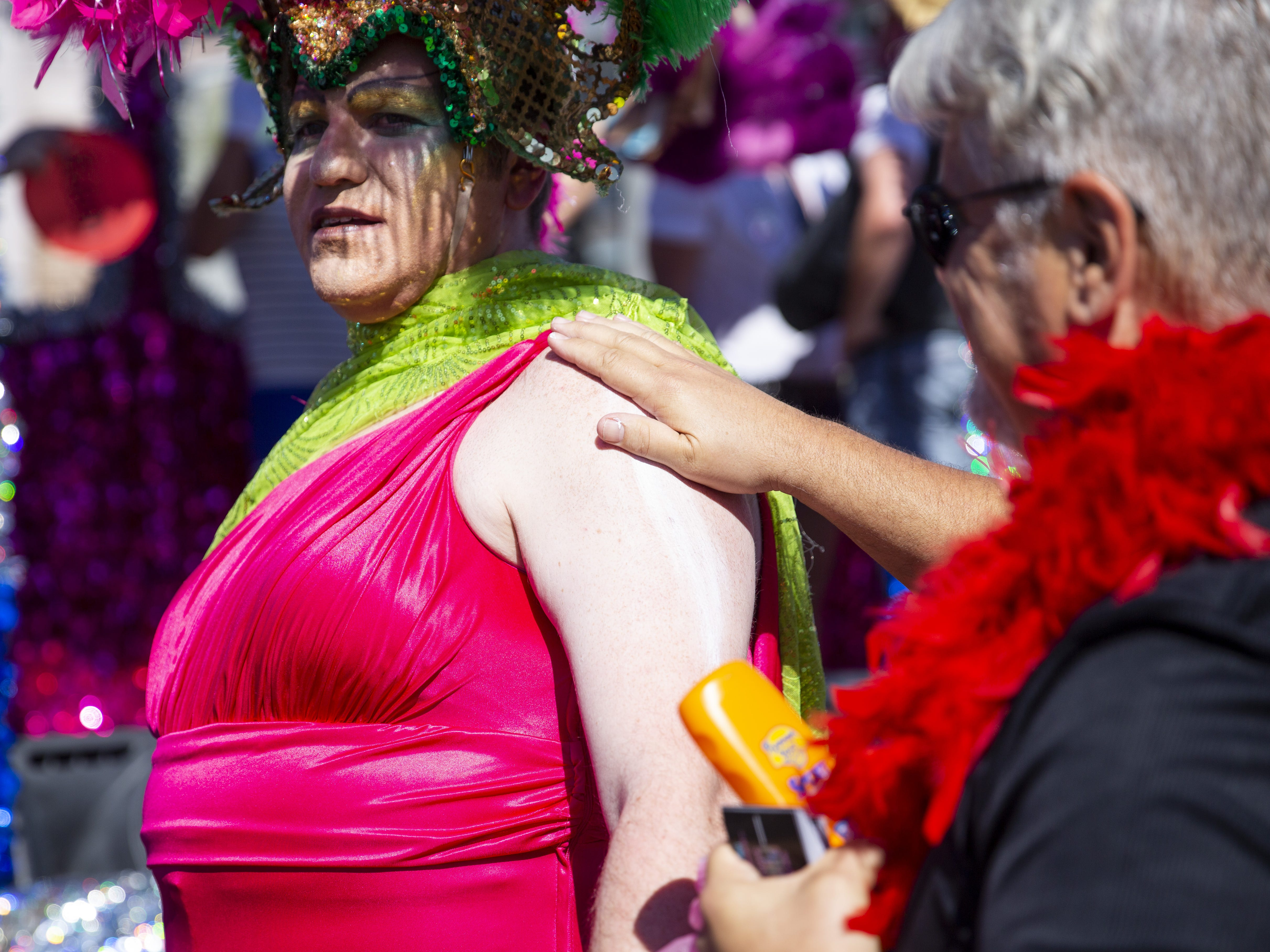 Scott Loos rubs sunscreen on one of the divas who marched at the front of the Phoenix Pride Parade on April 7, 2019.