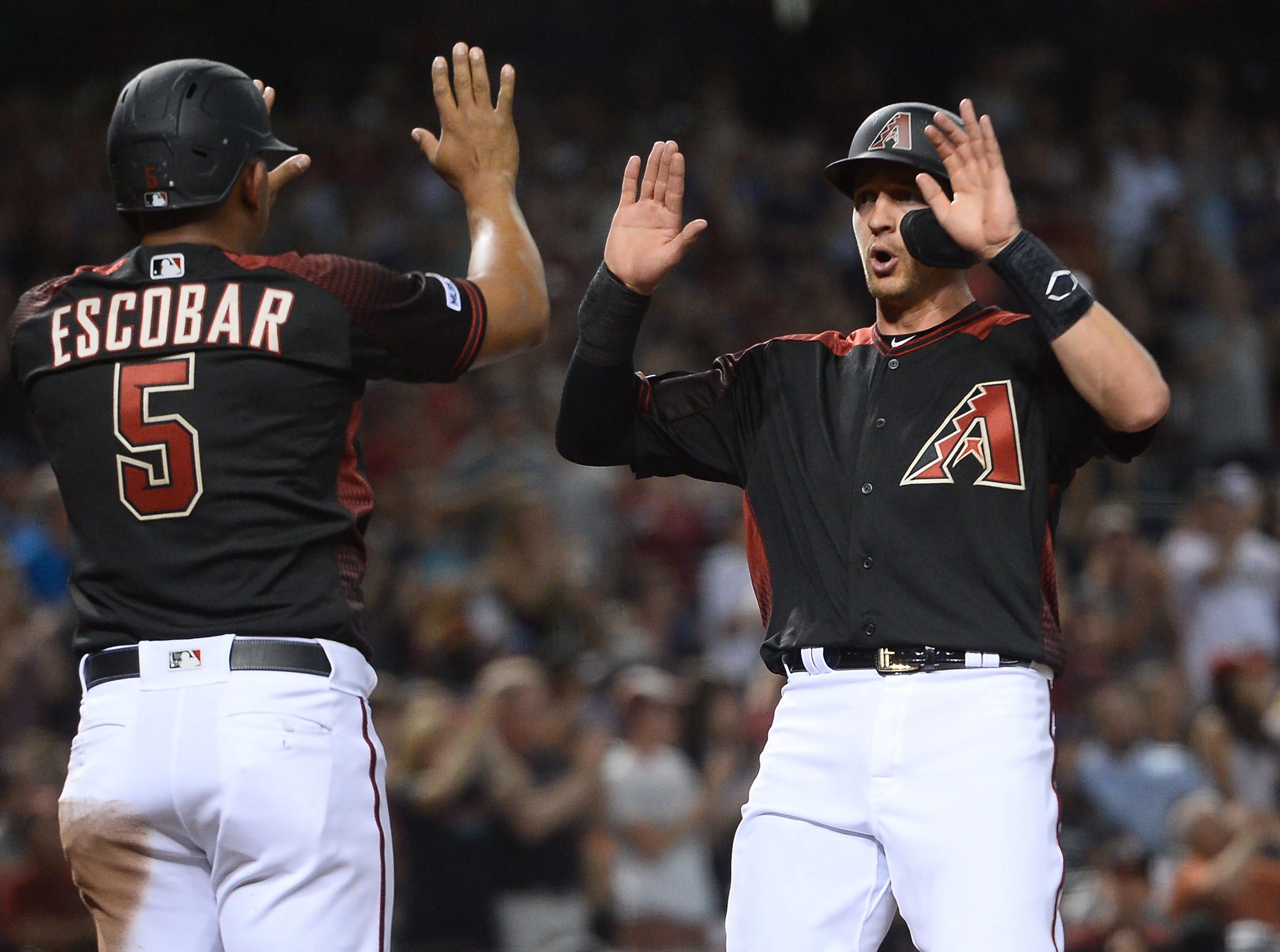 Apr 6, 2019; Phoenix, AZ, USA; Arizona Diamondbacks third baseman Eduardo Escobar (5) and Arizona Diamondbacks shortstop Nick Ahmed (13) slap hands after scoring runs against the Boston Red Sox during the second inning at Chase Field. Mandatory Credit: Joe Camporeale-USA TODAY Sports