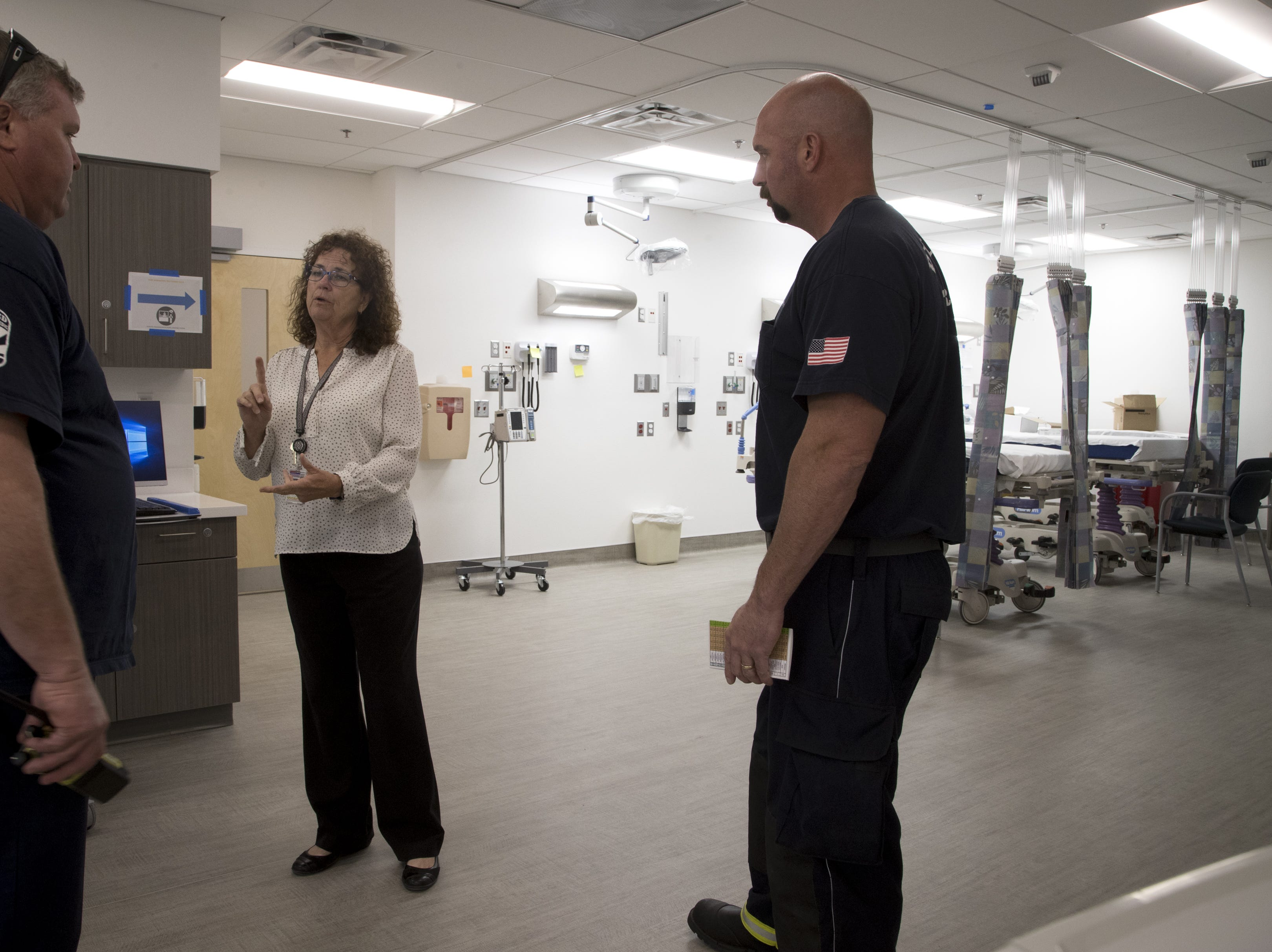Barb Bovee (center) gives Phoenix Fire Captain Rusty Stalder (left) and firefighter Luke Moran a tour of the Emergency Department at the Maricopa Integrated Health System Maryvale campus on April 1, 2019.