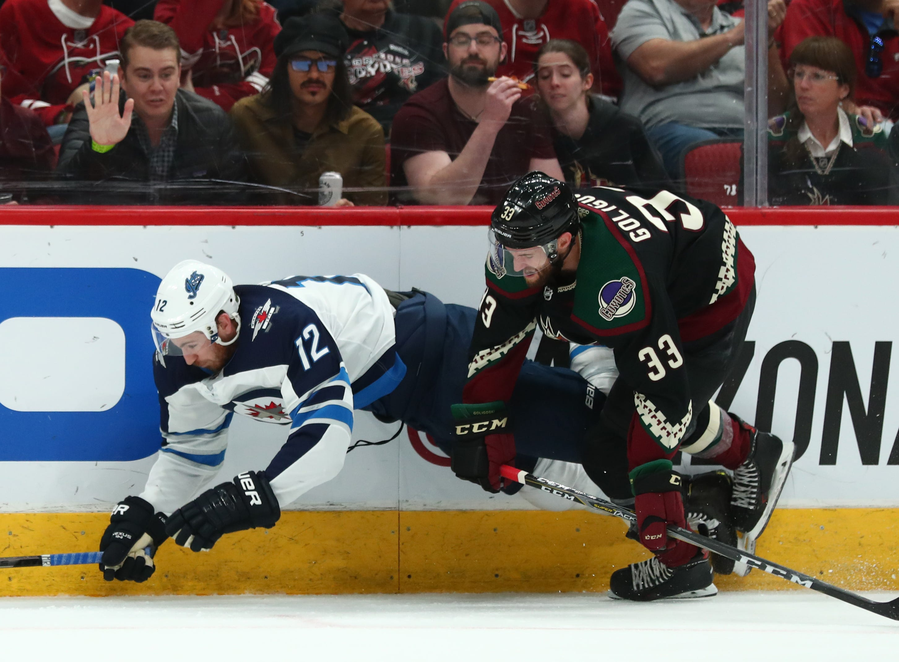 Apr 6, 2019; Glendale, AZ, USA; Winnipeg Jets center Kevin Hayes (12) falls as he is checked into the boards by Arizona Coyotes defenseman Alex Goligoski (33) in the second period at Gila River Arena. Mandatory Credit: Mark J. Rebilas-USA TODAY Sports
