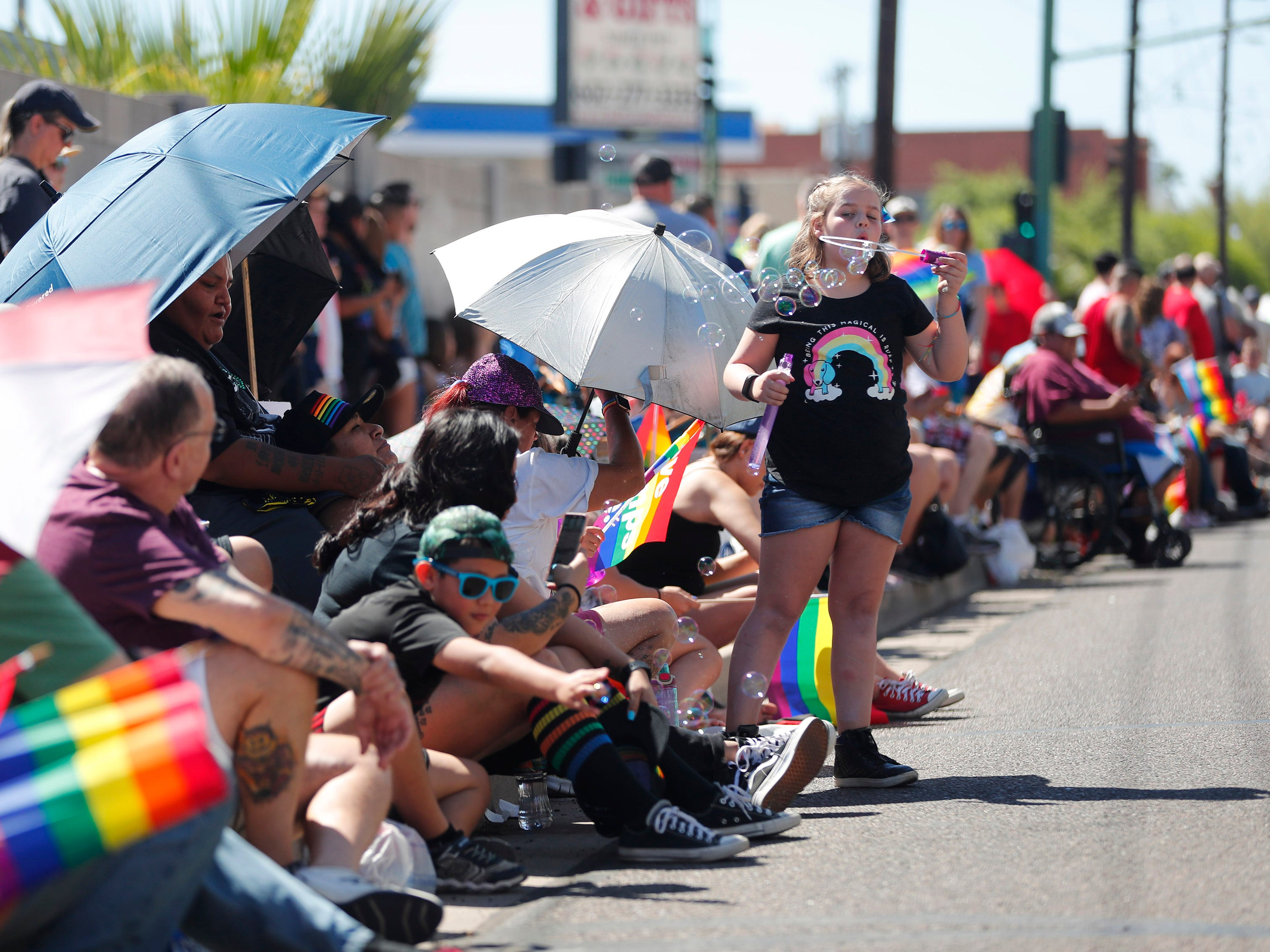 Sidney Henry , 9, blows bubbles during the Phoenix Pride Parade on April 7, 2019.