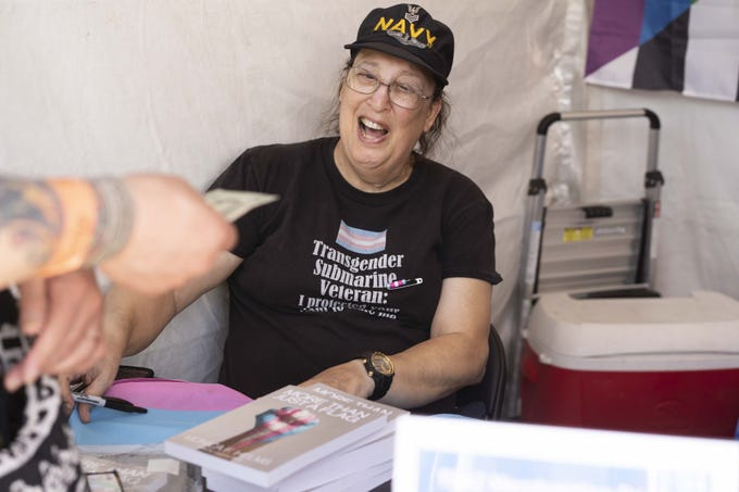 Monica Helms, creator of the transgender pride flag, signs books during Phoenix Pride at Steele Indian School Park on Saturday, April 6, 2019.