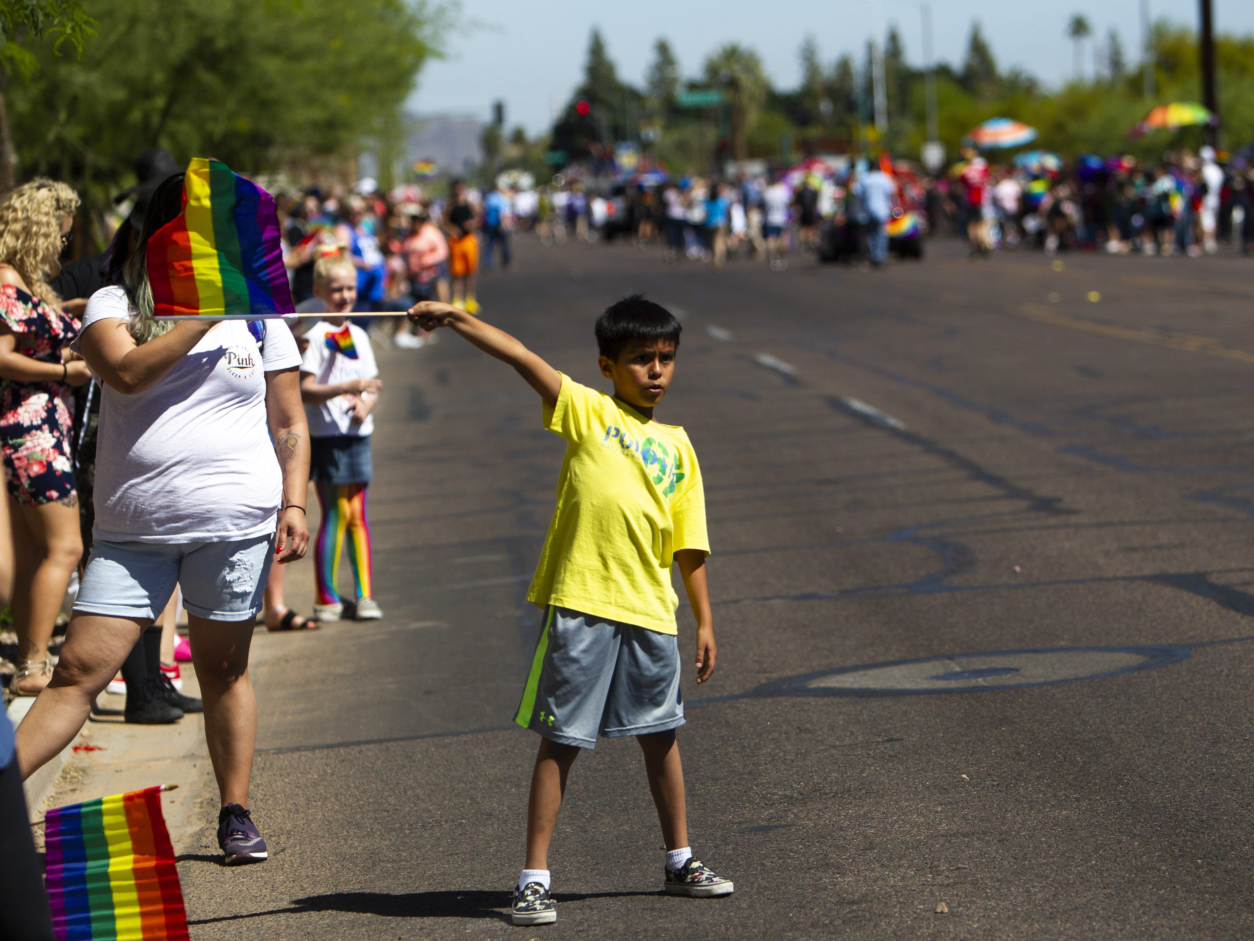 A boy waves a rainbow flag during the Phoenix Pride Parade on April 7, 2019.