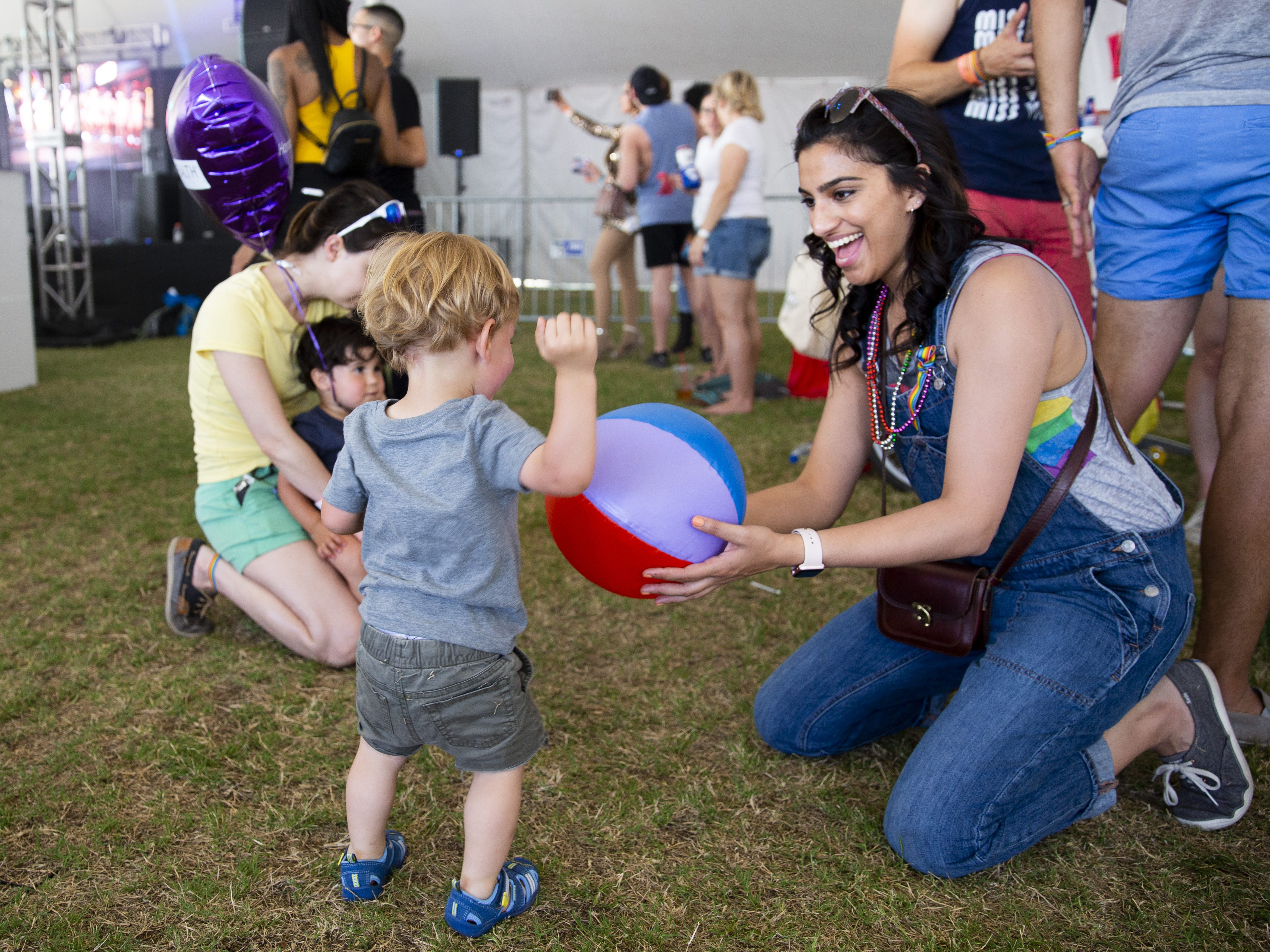 Shivani Desai offers a beach ball to Caellum Fontes, who is almost 2, during Phoenix Pride at Steele Indian School Park on Saturday, April 6, 2019.