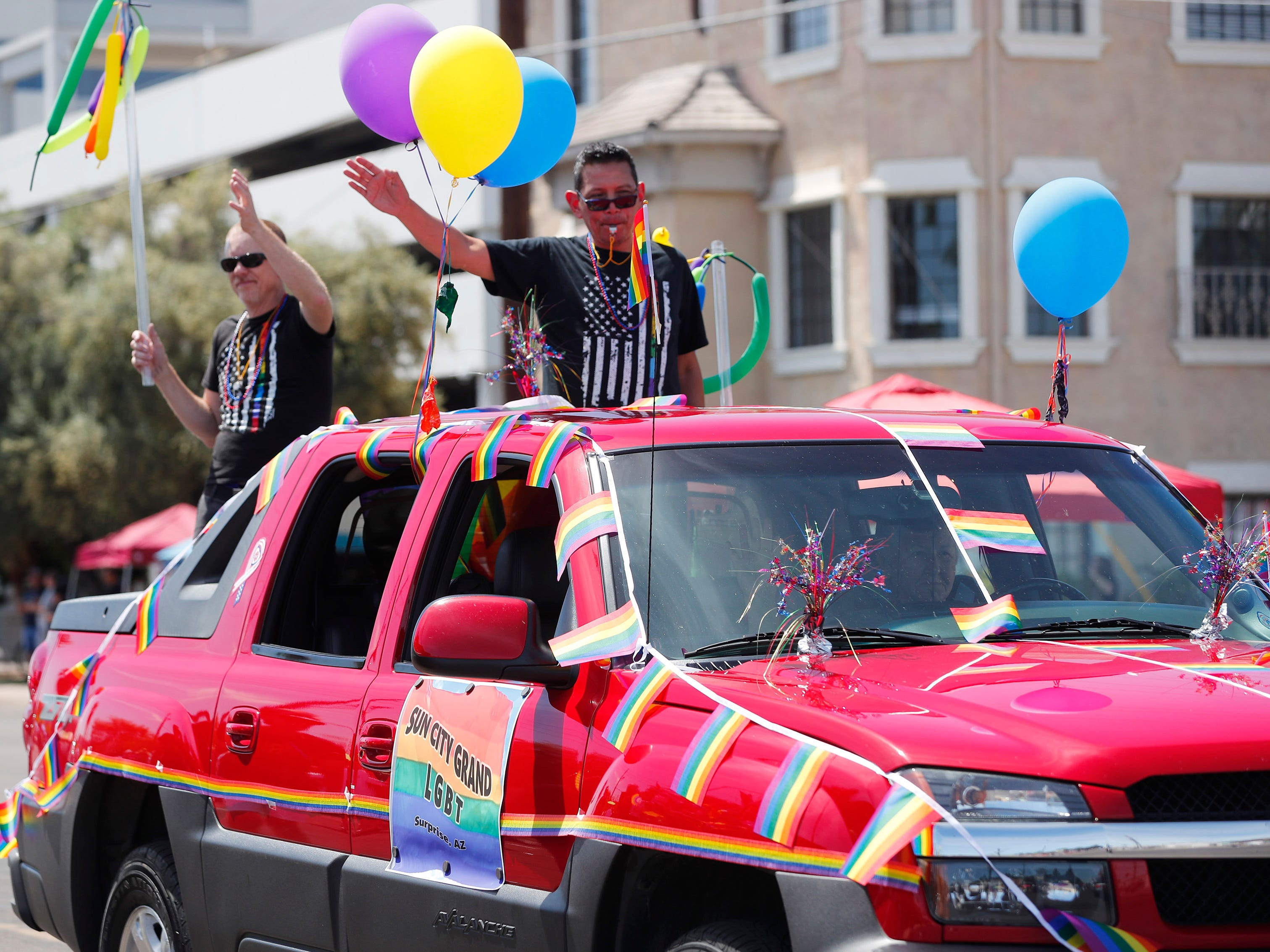 The Sun City Grand LGBT car waves during the Phoenix Pride Parade on April 7, 2019.
