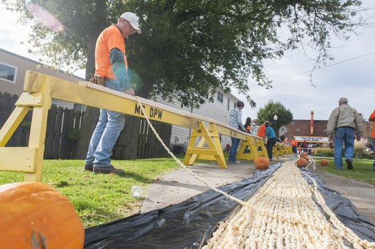 ANDREW JOWETT/TIMES HERALD Robert Arnold, a surveyor with BMJ Engineers and Surveyors, makes sure the length of the sections are measured correctly Oct. 17, 2016, in Marine City. Residents broke the record for longest string of popcorn with 1,200 feet.