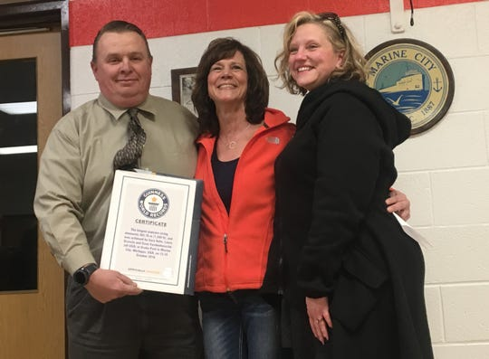 Mayor Dave Vandenbossche, from left, Laura Scaccia, owner of the Mariner Theater, and Erika DeLange, executive director of the Marine City Area Chamber of Commerce, stand with a certificate on Thursday, April 4, 2019, recognizing Marine City's  October 2016 recording-breaking string of popcorn.