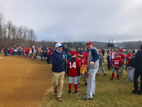 Members of the Hyde Park Little League (players, coaches and parents) take the field before a pre-game ceremony to honor former longtime coach Wayne Belcher, who died suddenly in December 2018.